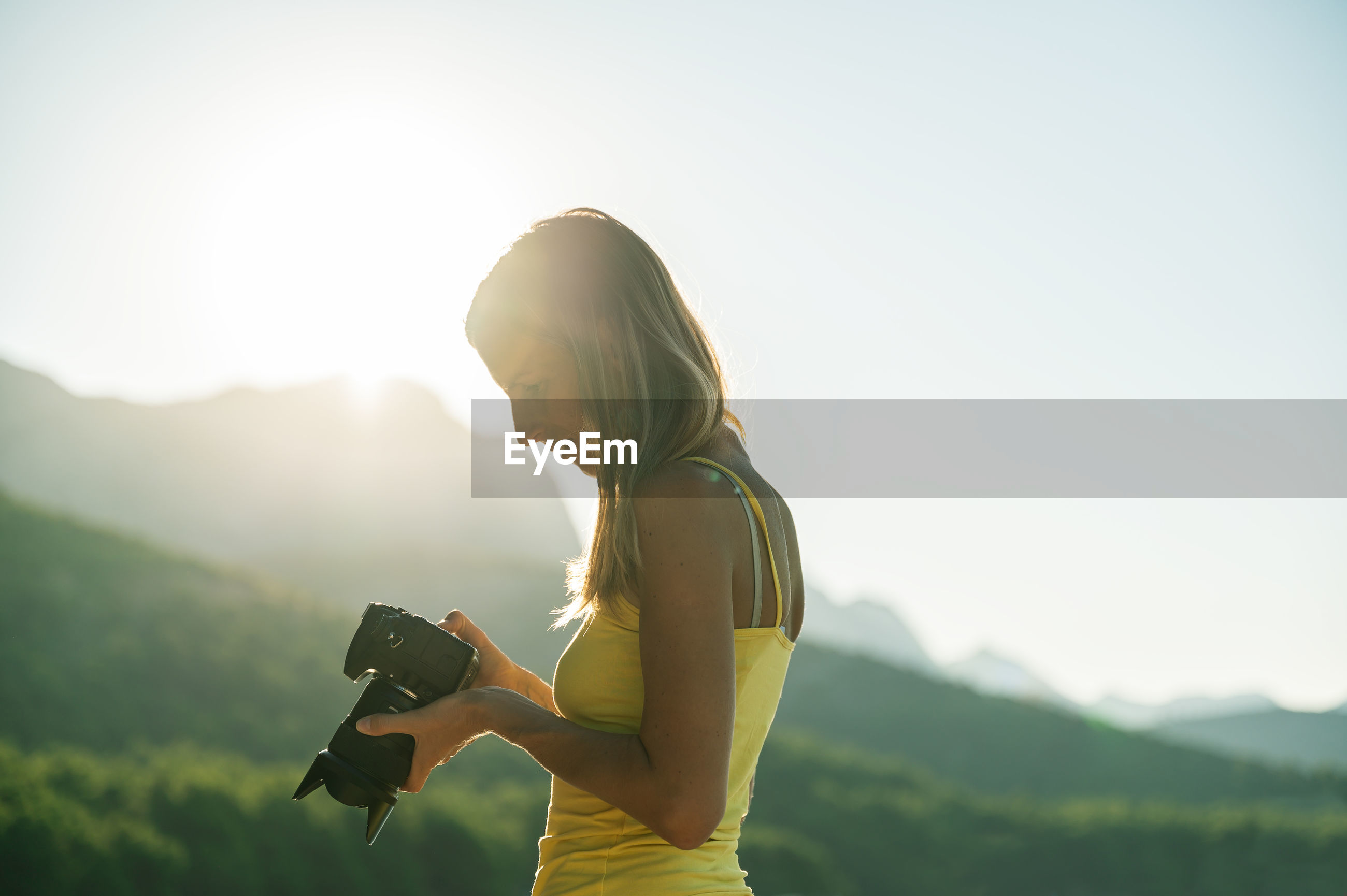 SIDE VIEW OF WOMAN PHOTOGRAPHING CAMERA AGAINST SKY