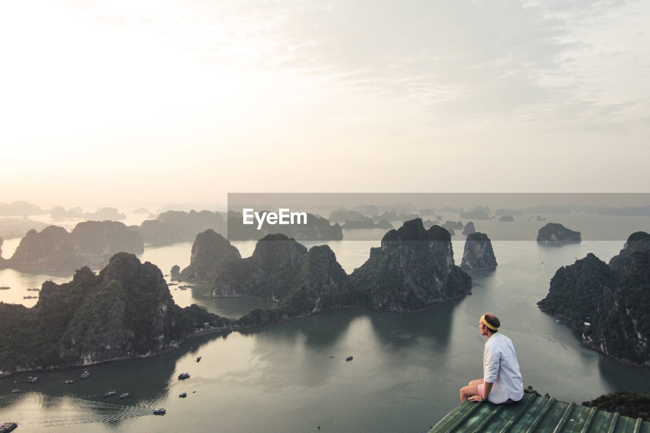 High Angle View Of Man Sitting At Observation Point By River