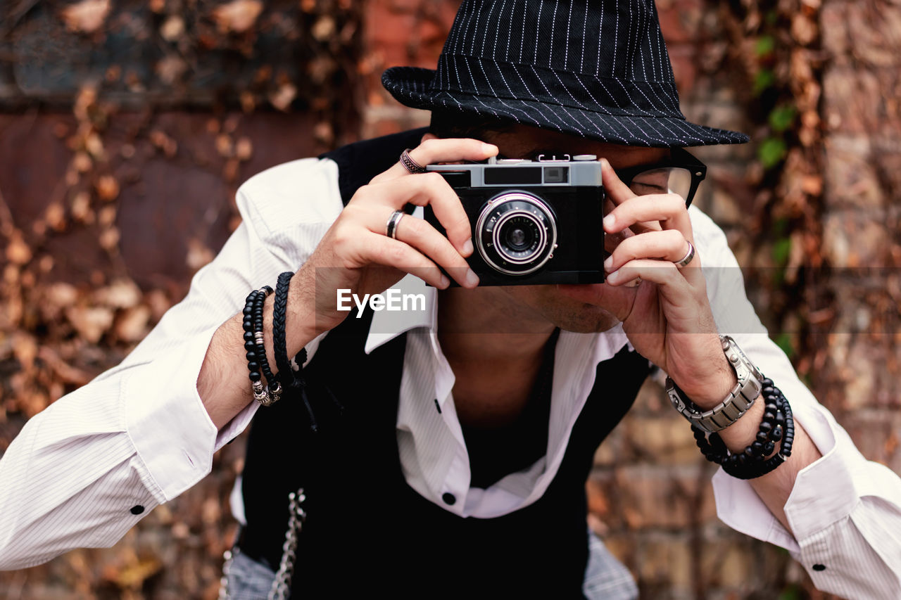 Close-up of photographer using analog photo camera while taking picture outdoors.