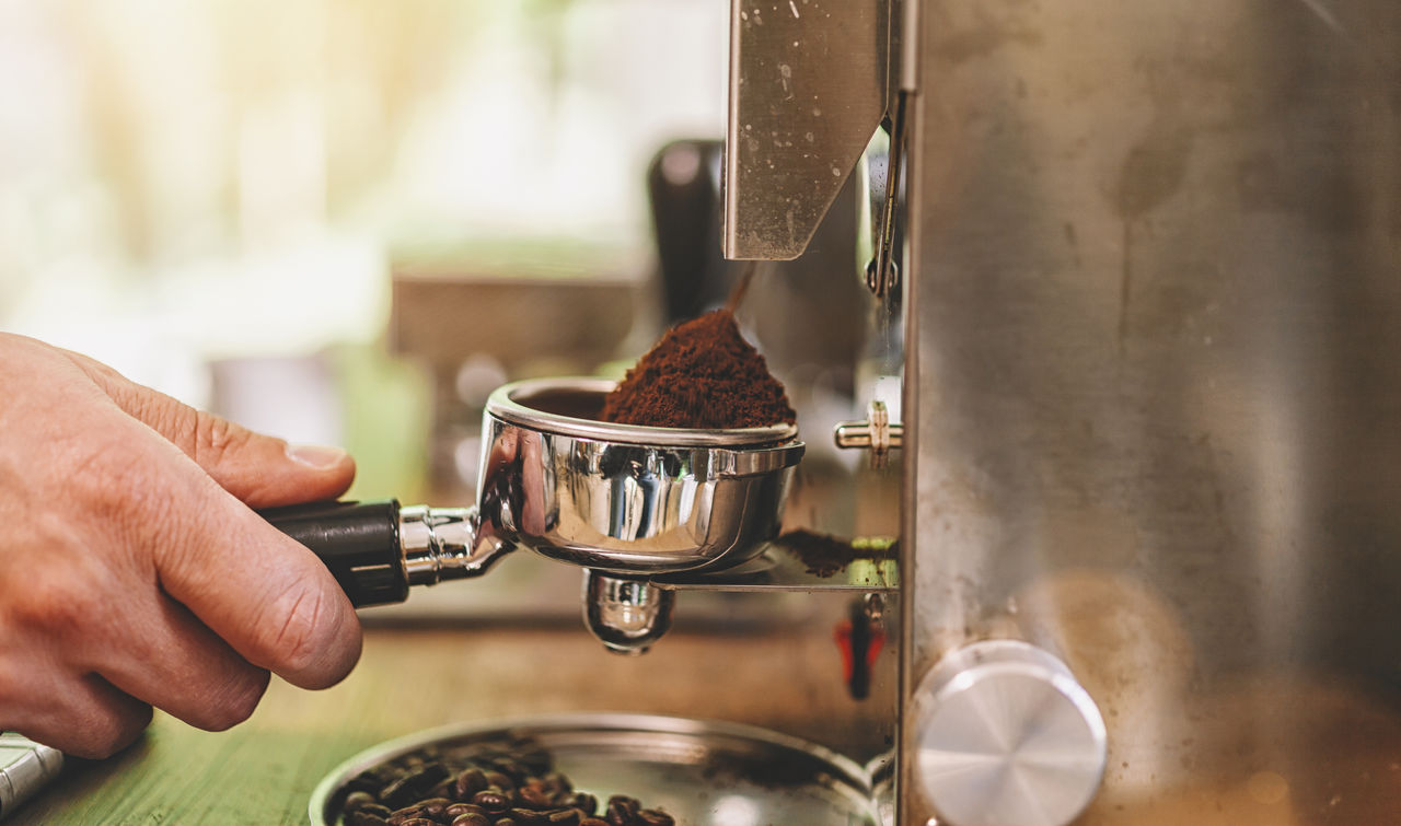hand, human hand, food and drink, real people, coffee maker, one person, human body part, coffee, holding, drink, indoors, coffee - drink, refreshment, preparation, selective focus, cup, appliance, close-up, mug, machinery, finger, coffee shop