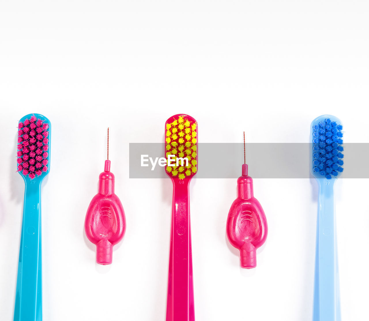 Close-Up Of Colorful Toothbrushes Arranged Over White Background