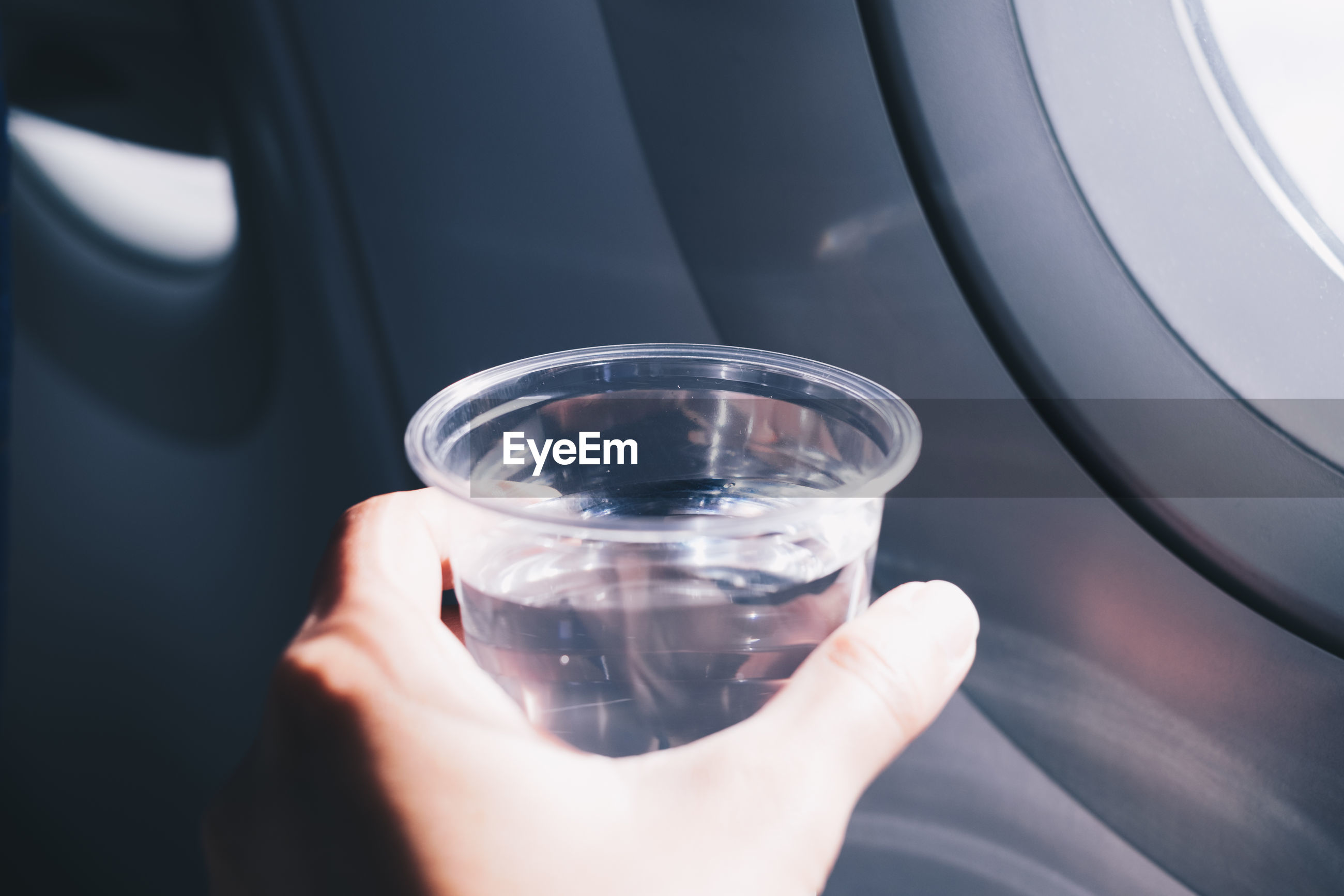 Cropped hand holding glass of water in car