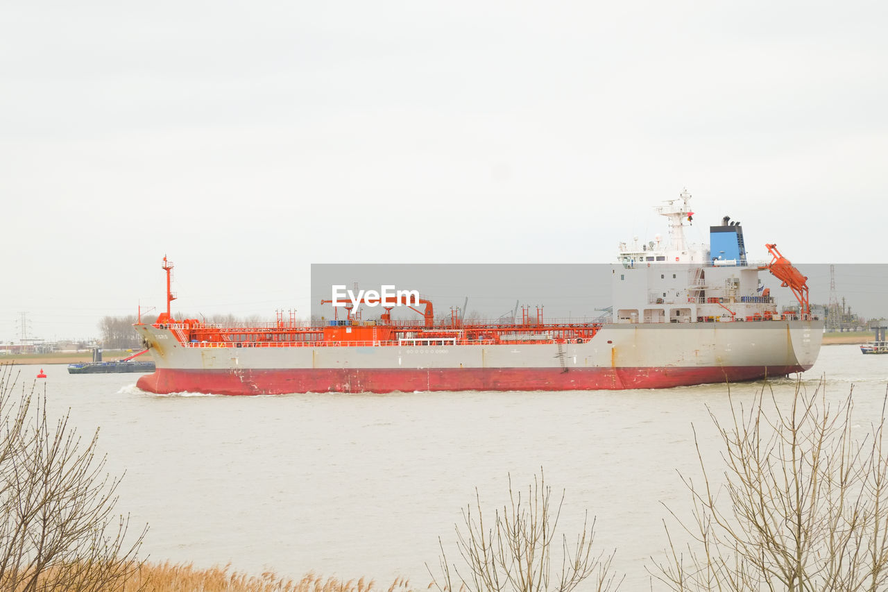 water, nautical vessel, sky, transportation, ship, nature, mode of transportation, freight transportation, day, sea, red, business, no people, shipping, industry, architecture, outdoors, container ship, waterfront