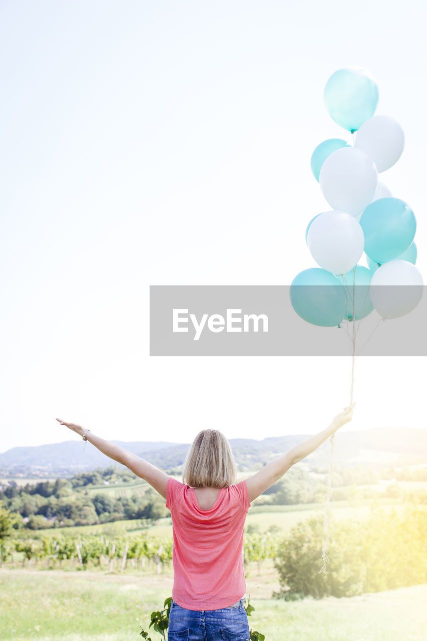 sky, rear view, real people, balloon, women, leisure activity, lifestyles, field, human arm, one person, land, nature, clear sky, environment, casual clothing, arms outstretched, limb, arms raised, copy space, hair, hairstyle, freedom, outdoors