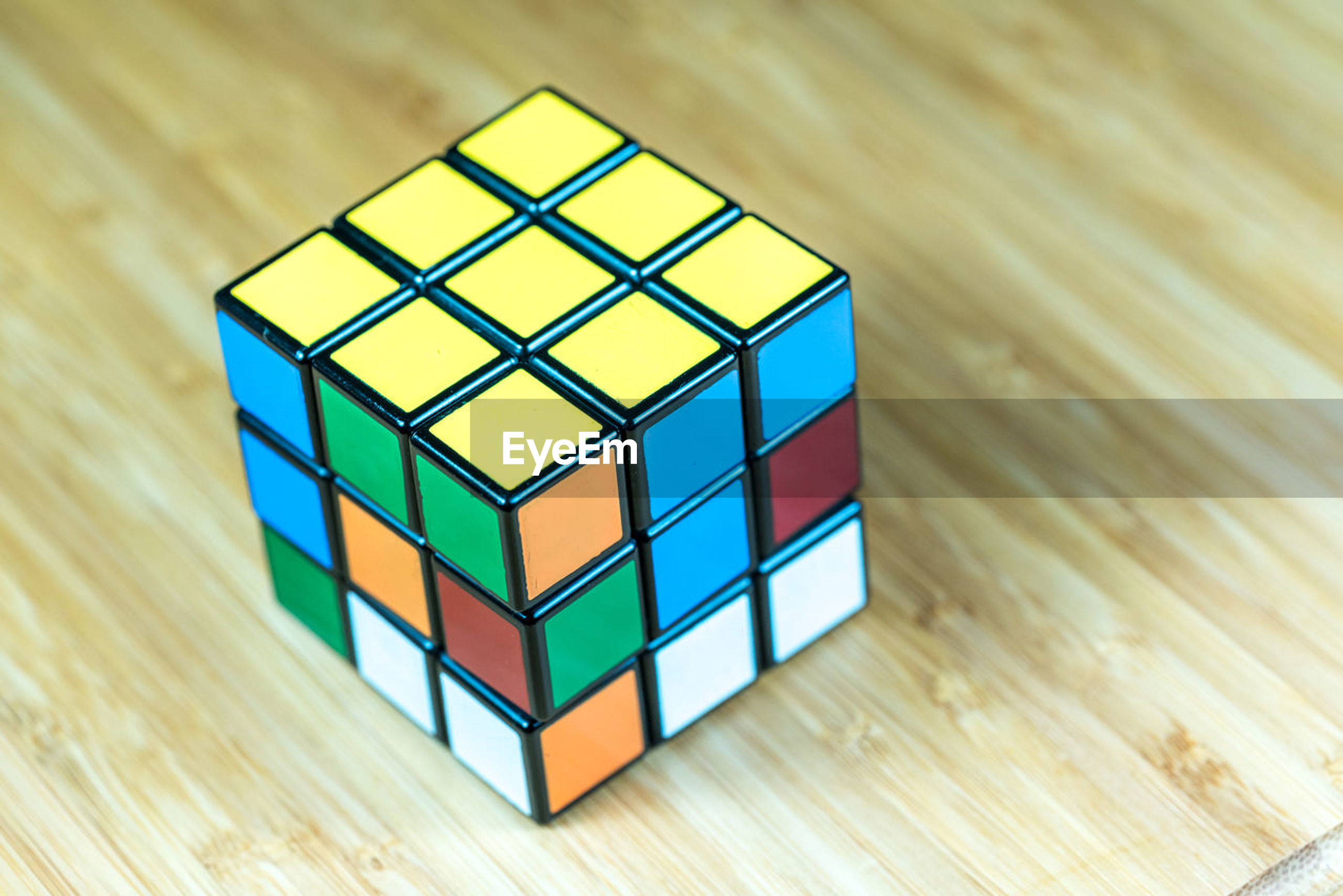 wood - material, indoors, geometric shape, shape, toy block, still life, multi colored, square shape, puzzle, table, high angle view, pattern, no people, focus on foreground, close-up, strategy, yellow, leisure games, day