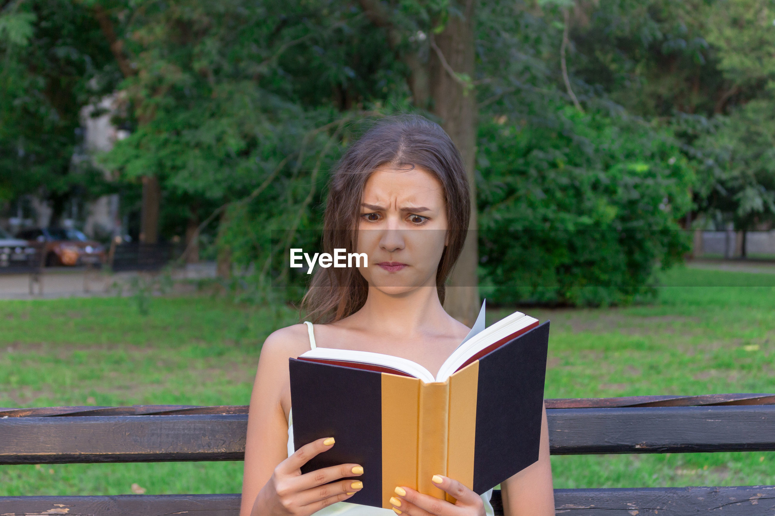 Shocked young woman reading book while sitting on bench in park