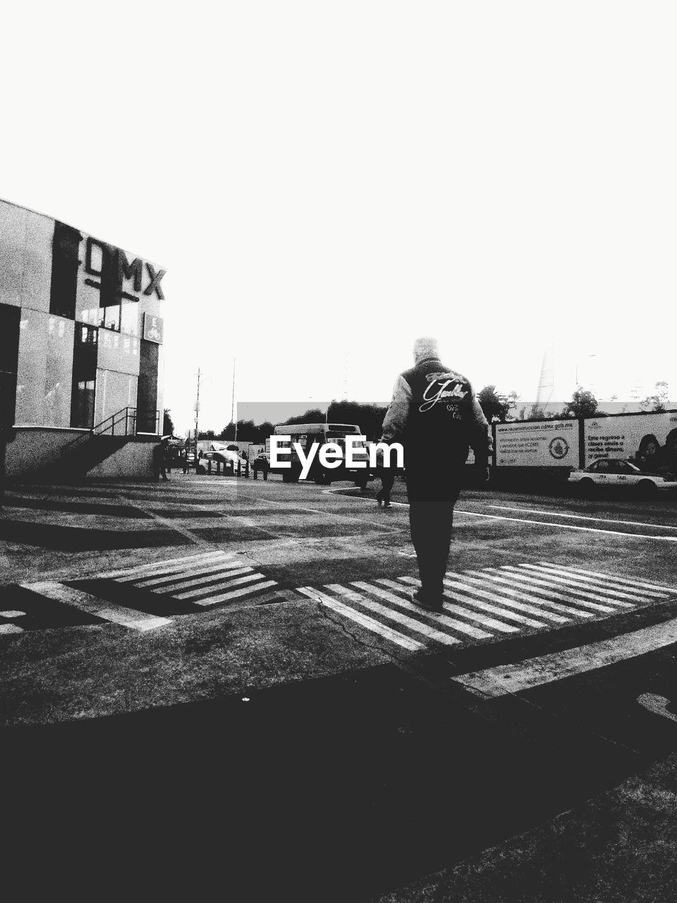 REAR VIEW OF MAN WALKING ON STREET IN CITY AGAINST SKY
