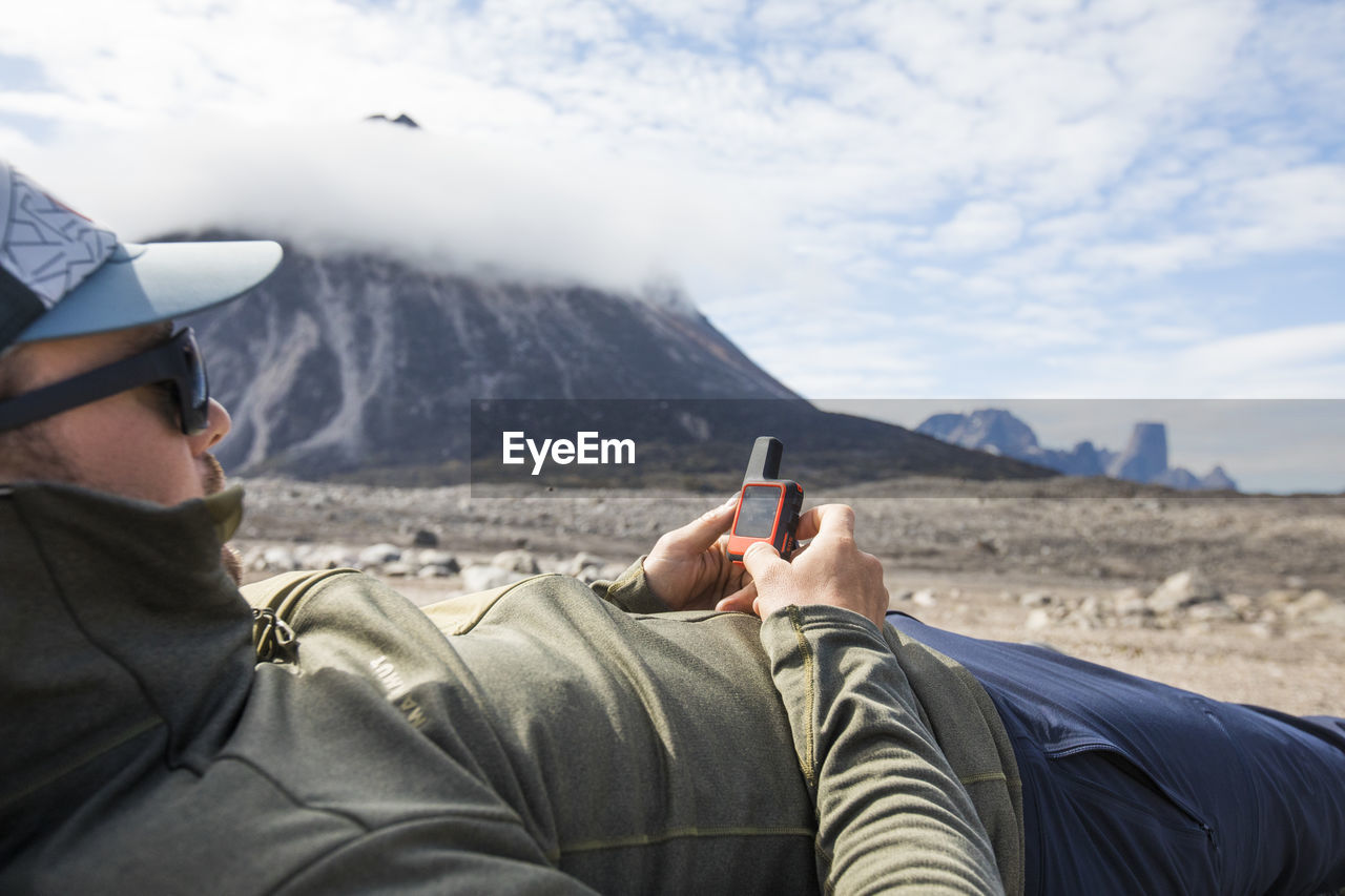 MAN USING MOBILE PHONE AGAINST MOUNTAINS
