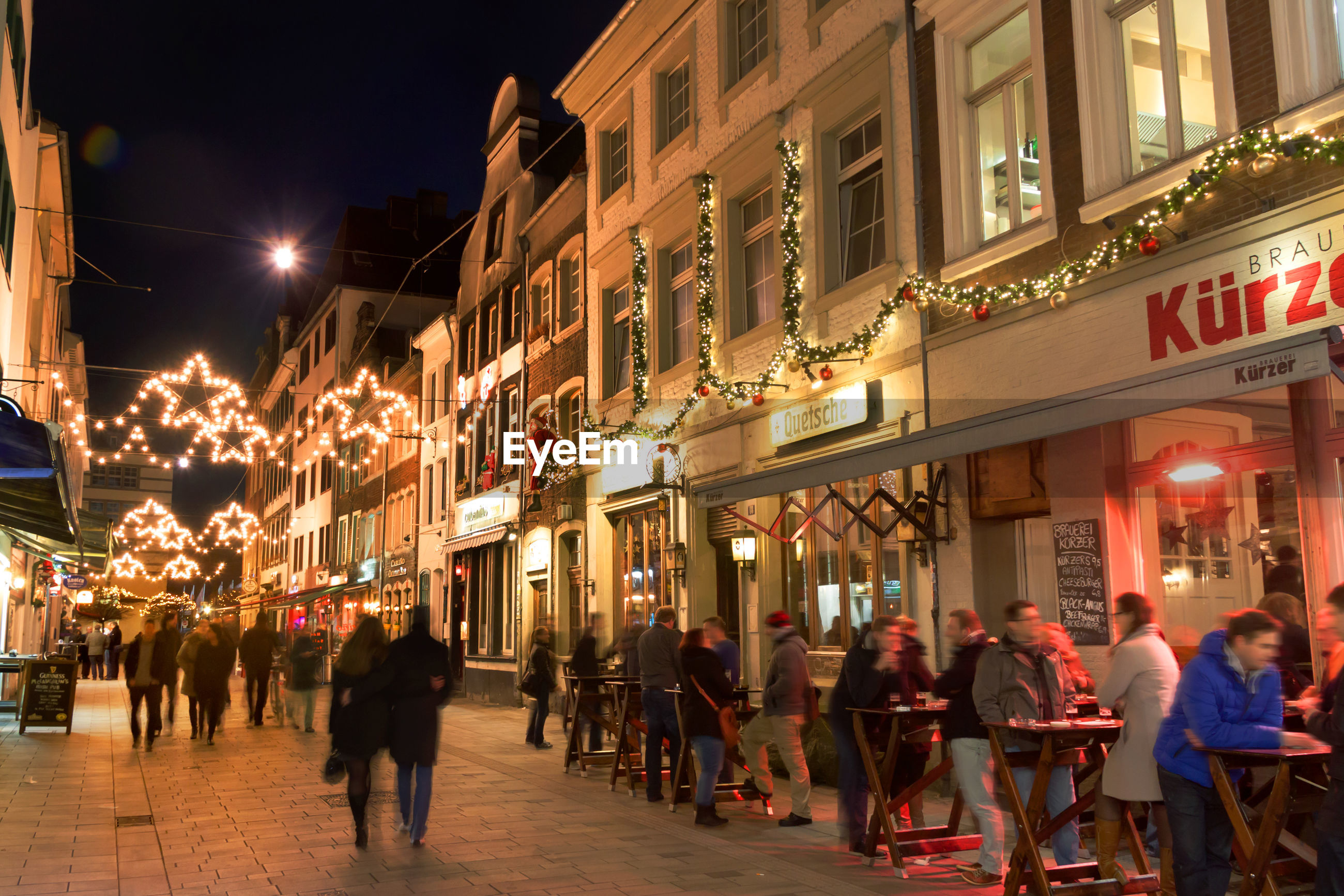 large group of people, men, building exterior, person, city, architecture, leisure activity, built structure, lifestyles, city life, walking, illuminated, city street, retail, sky, outdoors