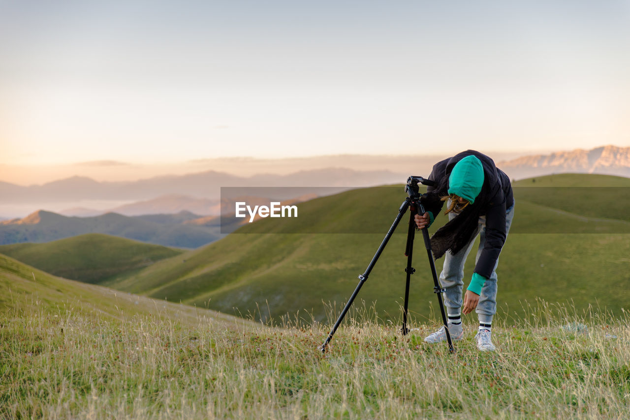 nature, one person, real people, beauty in nature, mountain, leisure activity, lifestyles, grass, sunset, outdoors, scenics, tranquil scene, full length, holding, camera - photographic equipment, mountain range, hiking, standing, landscape, sky, women, photography themes, day, golf course, adult, people