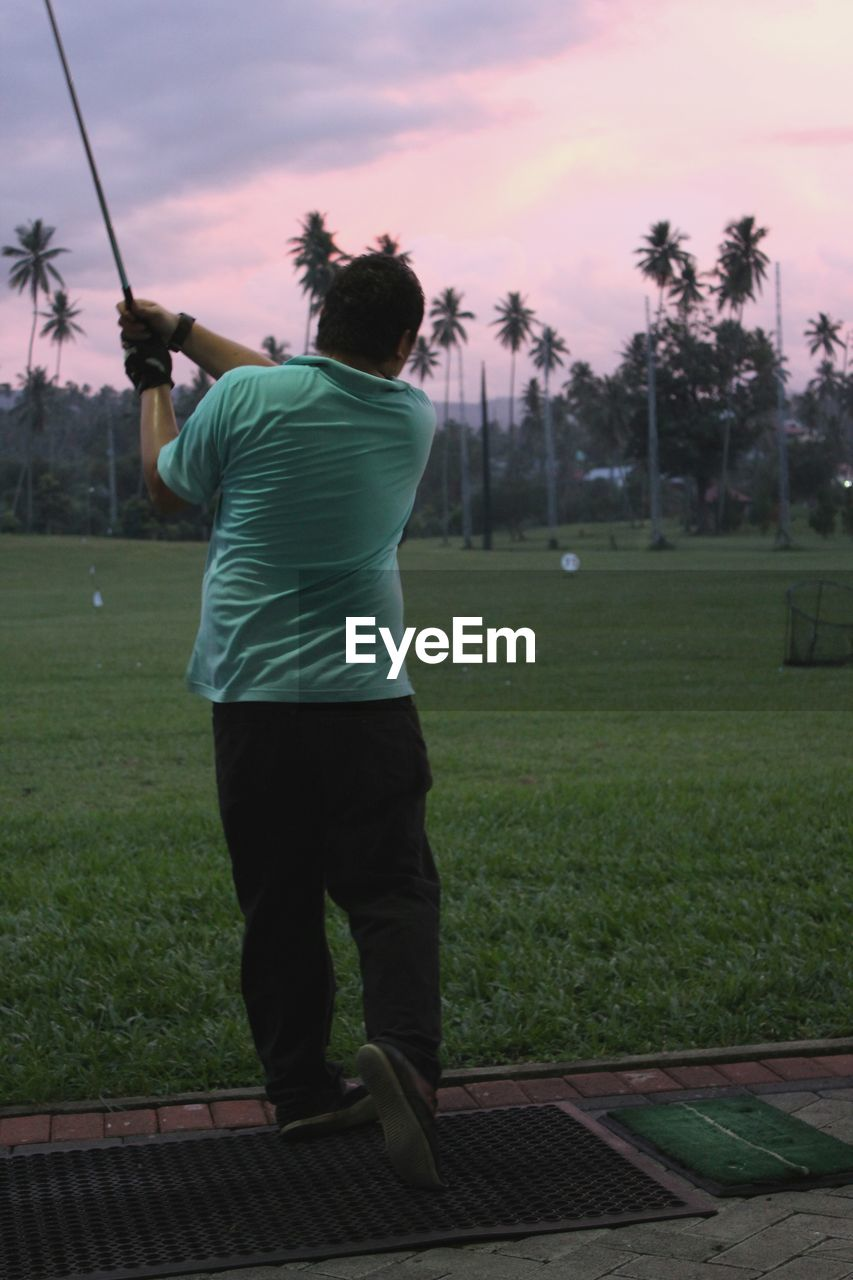 Golfer Playing On Field At Dusk