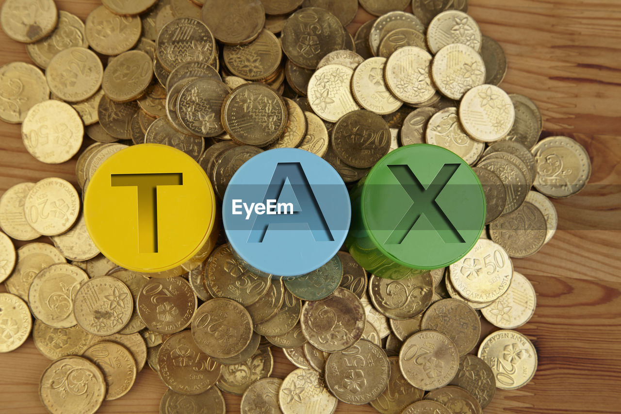 High angle view of containers with tax text amidst coins on table