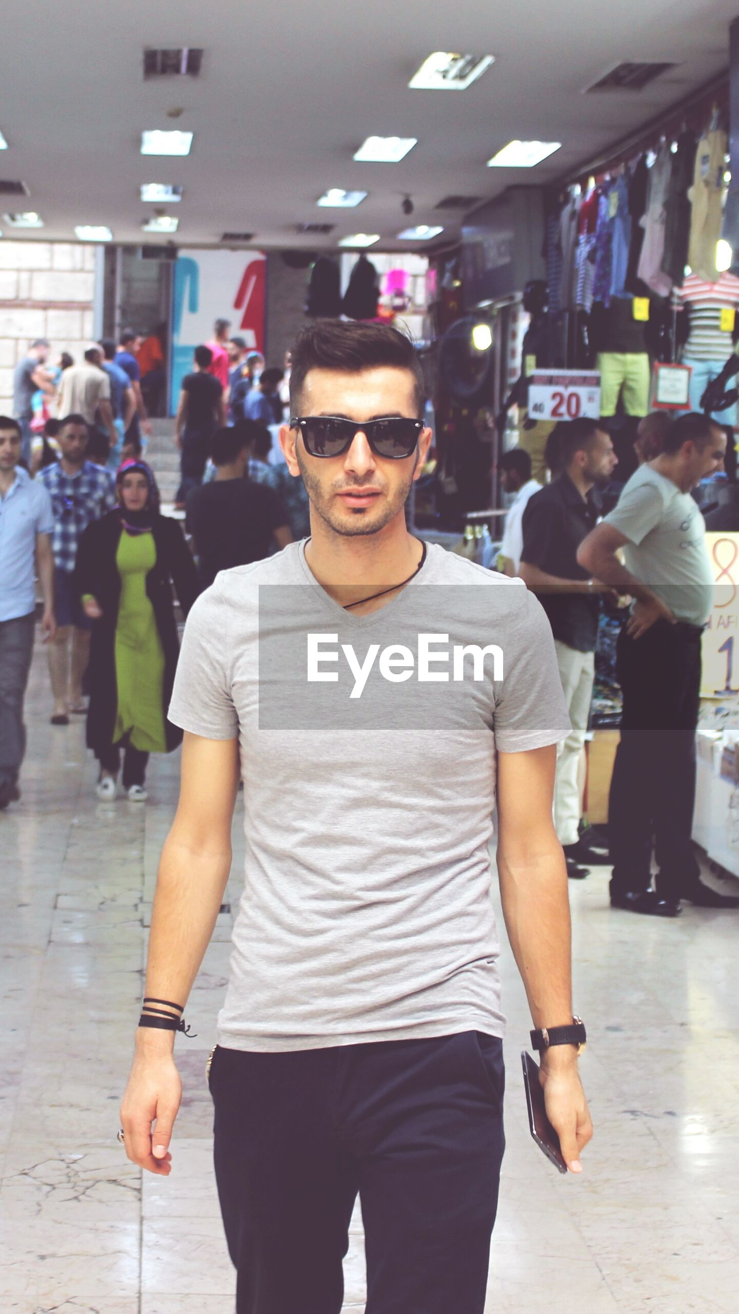 lifestyles, indoors, casual clothing, young adult, standing, leisure activity, front view, young men, portrait, looking at camera, person, three quarter length, technology, holding, communication, sunglasses, photography themes, waist up