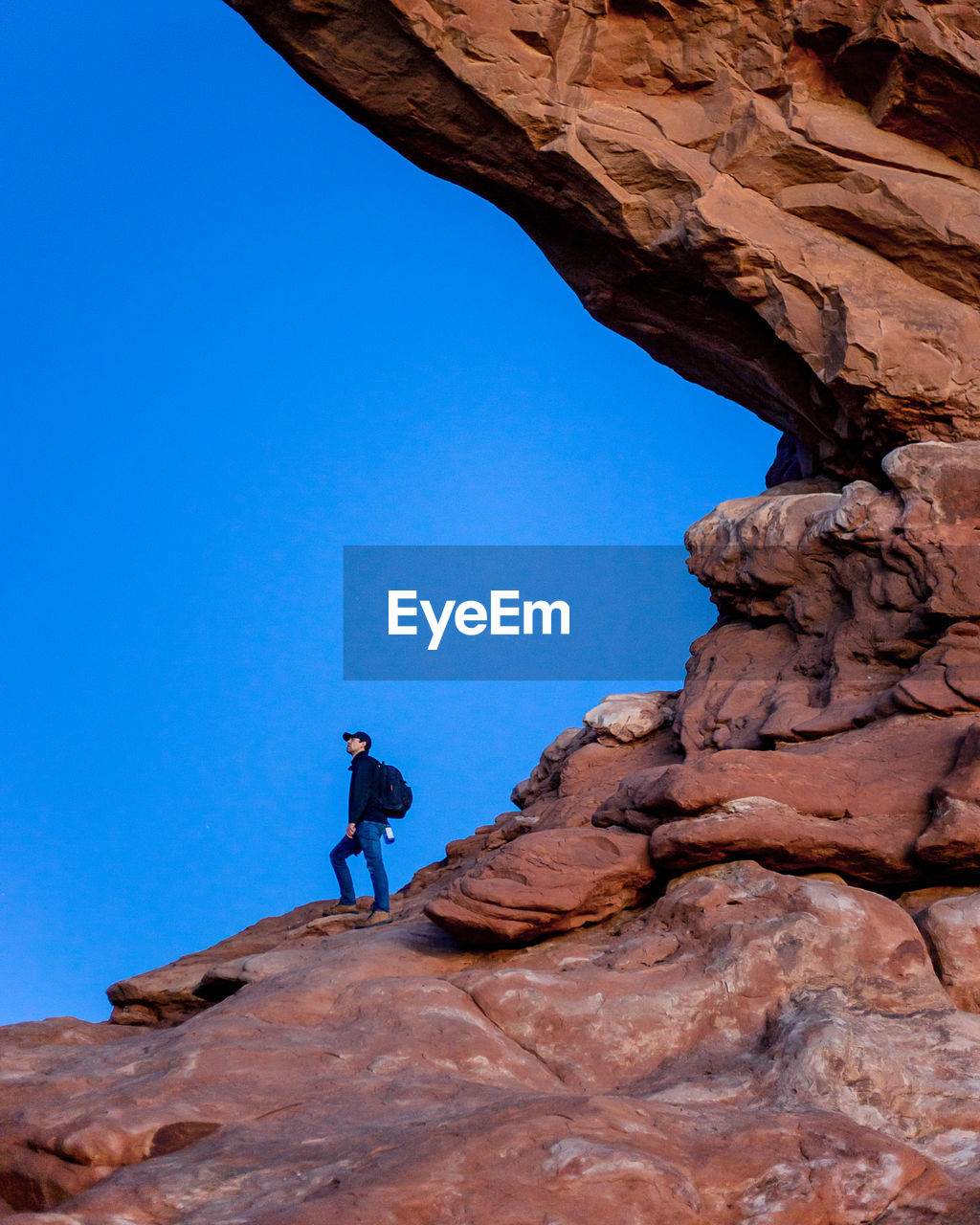 LOW ANGLE VIEW OF MAN AGAINST ROCK FORMATION