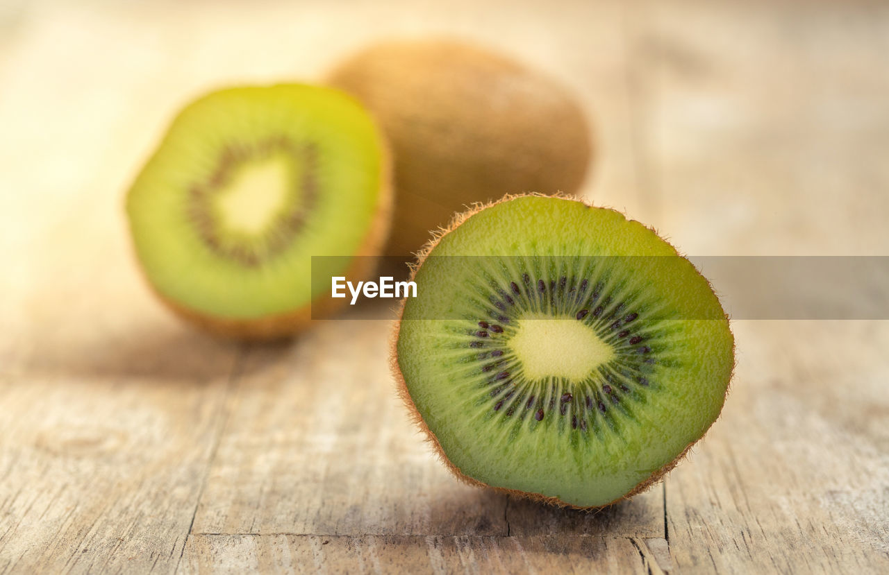 healthy eating, food and drink, food, freshness, kiwi, still life, kiwi - fruit, table, wellbeing, fruit, cross section, close-up, slice, no people, wood - material, indoors, green color, focus on foreground, selective focus, halved