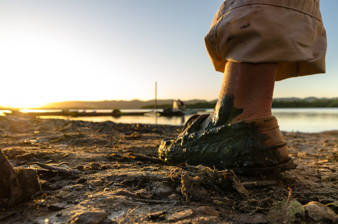 Persons Muddy Foot Wading On Riverbank