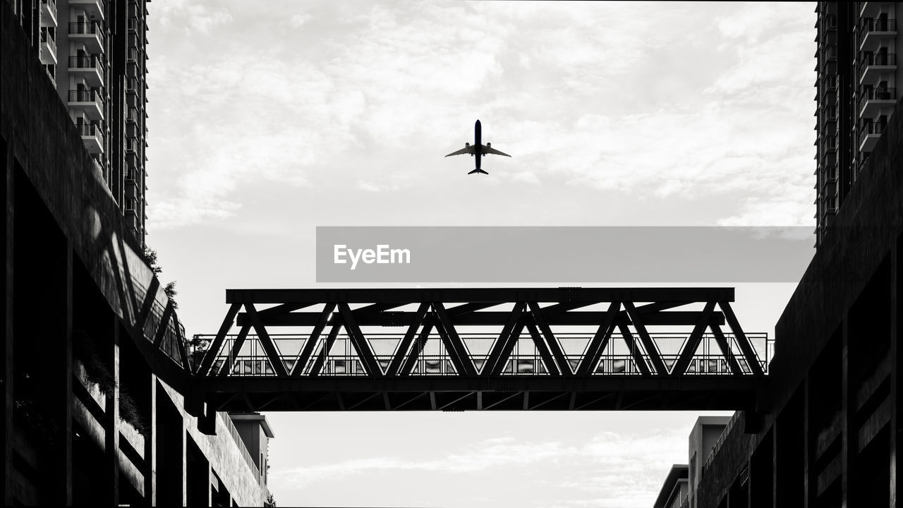 Low angle view of airplane flying over silhouette bridge