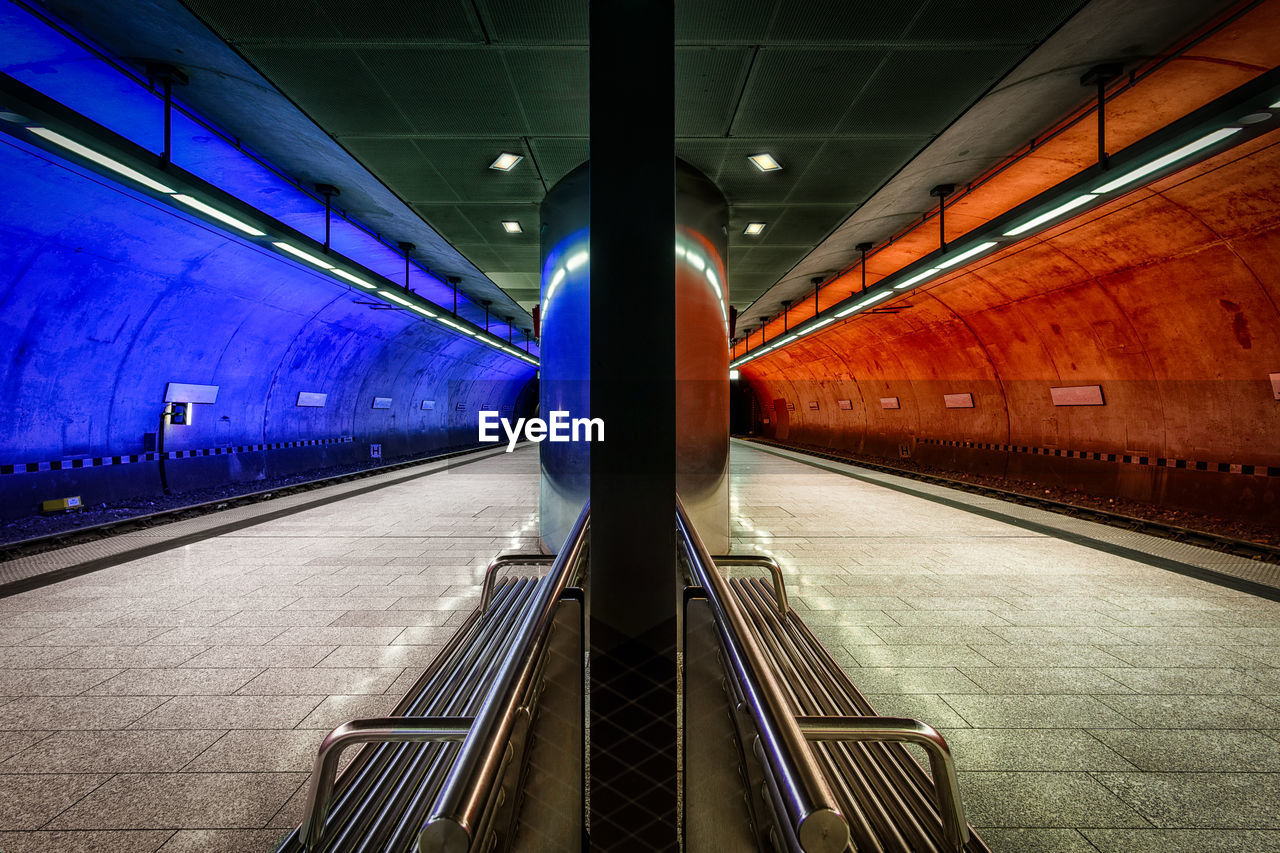 illuminated, indoors, transportation, architecture, lighting equipment, public transportation, the way forward, ceiling, subway station, rail transportation, built structure, direction, railing, empty, flooring, mode of transportation, travel, technology, no people, diminishing perspective, modern, moving walkway, light, architectural column