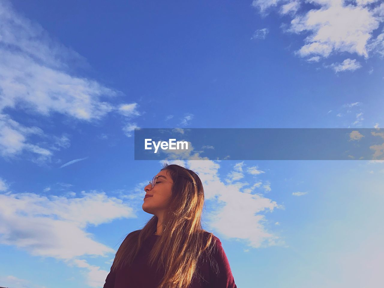 Low angle view of young woman against blue sky