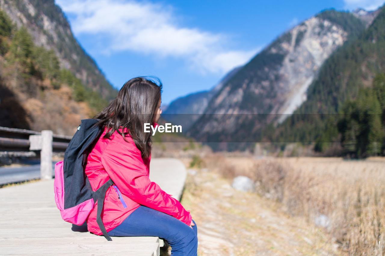 Side View Of Girl With Backpack Sitting On Field Against Mountain