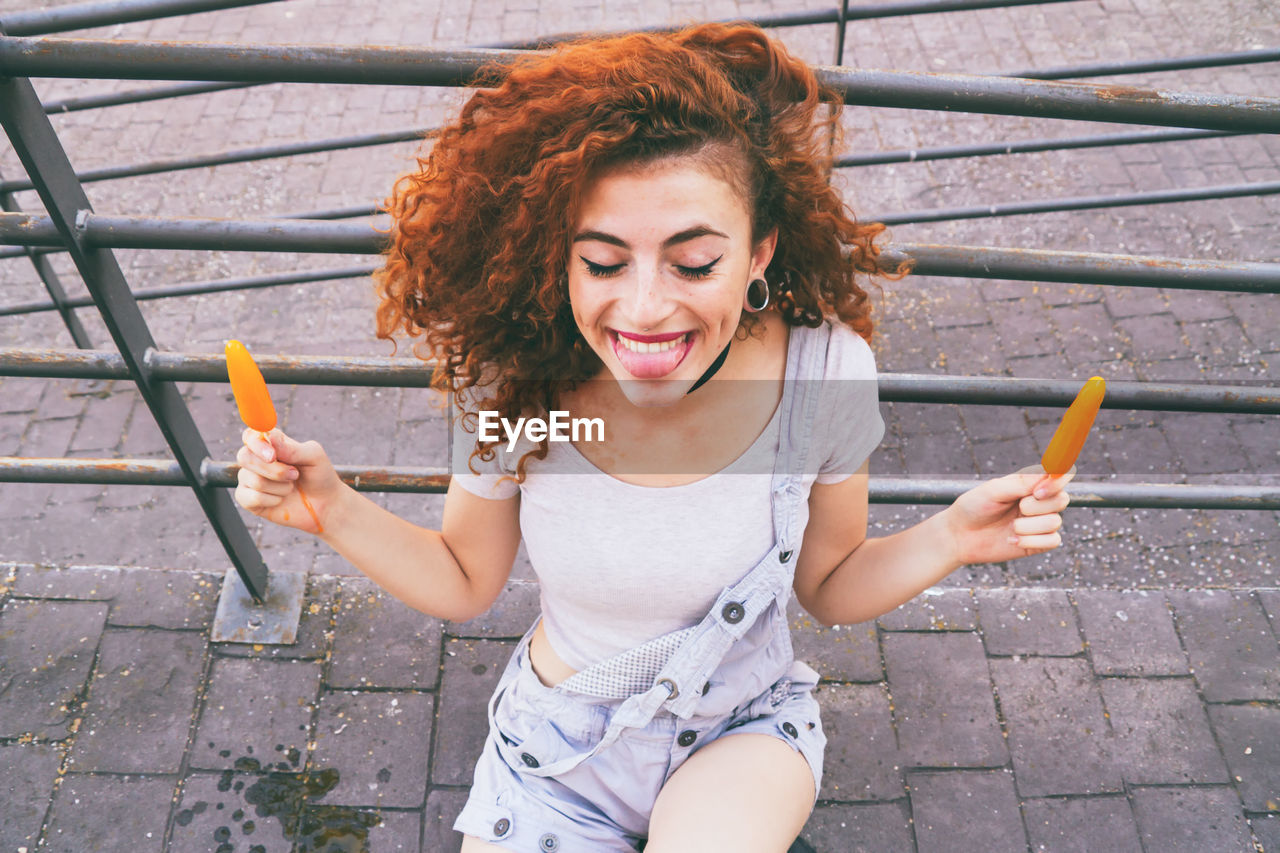 High Angle View Of Happy Woman Having Orange Popsicles On Footpath