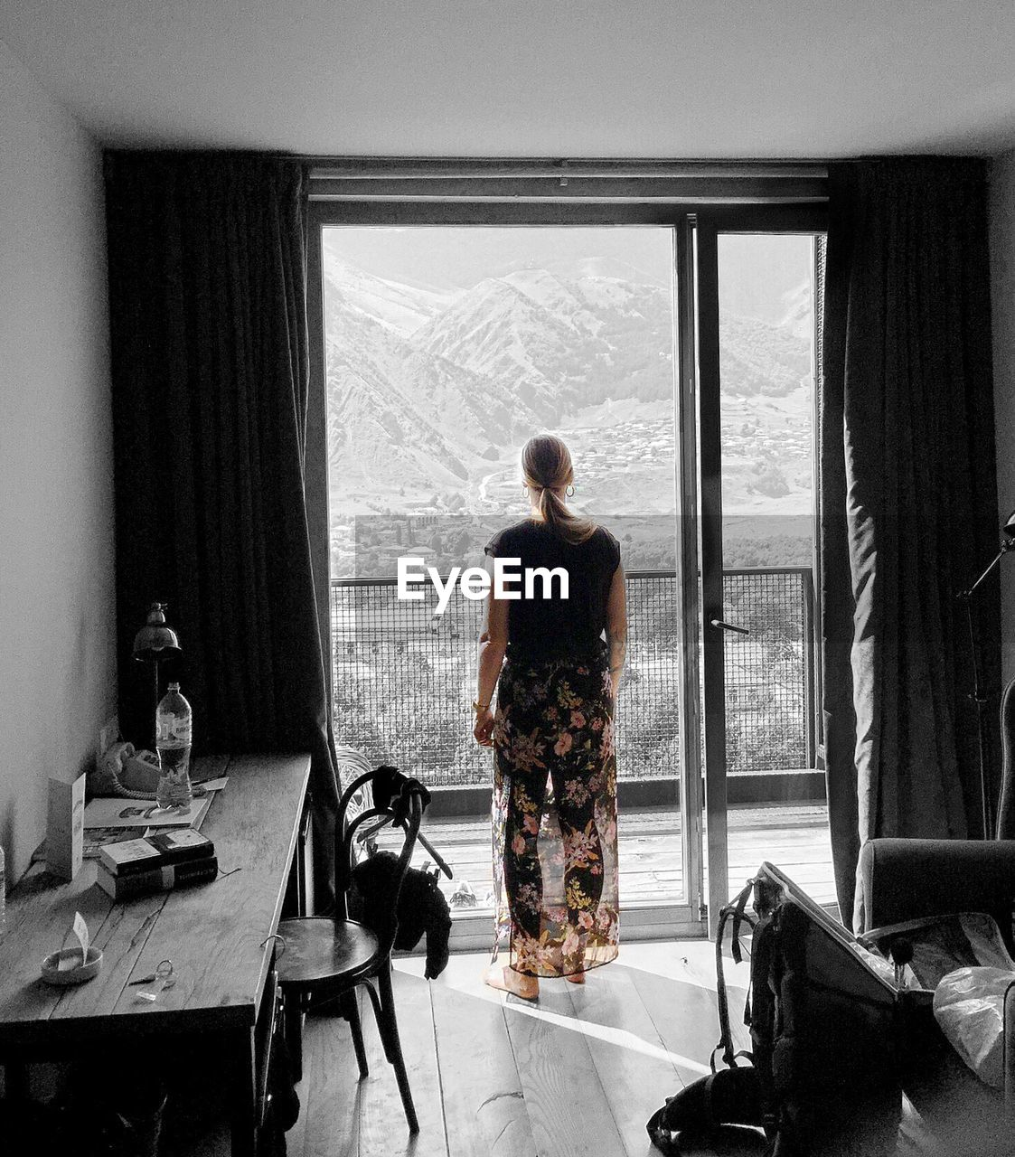 Rear View Of Woman Standing Against Window At Home