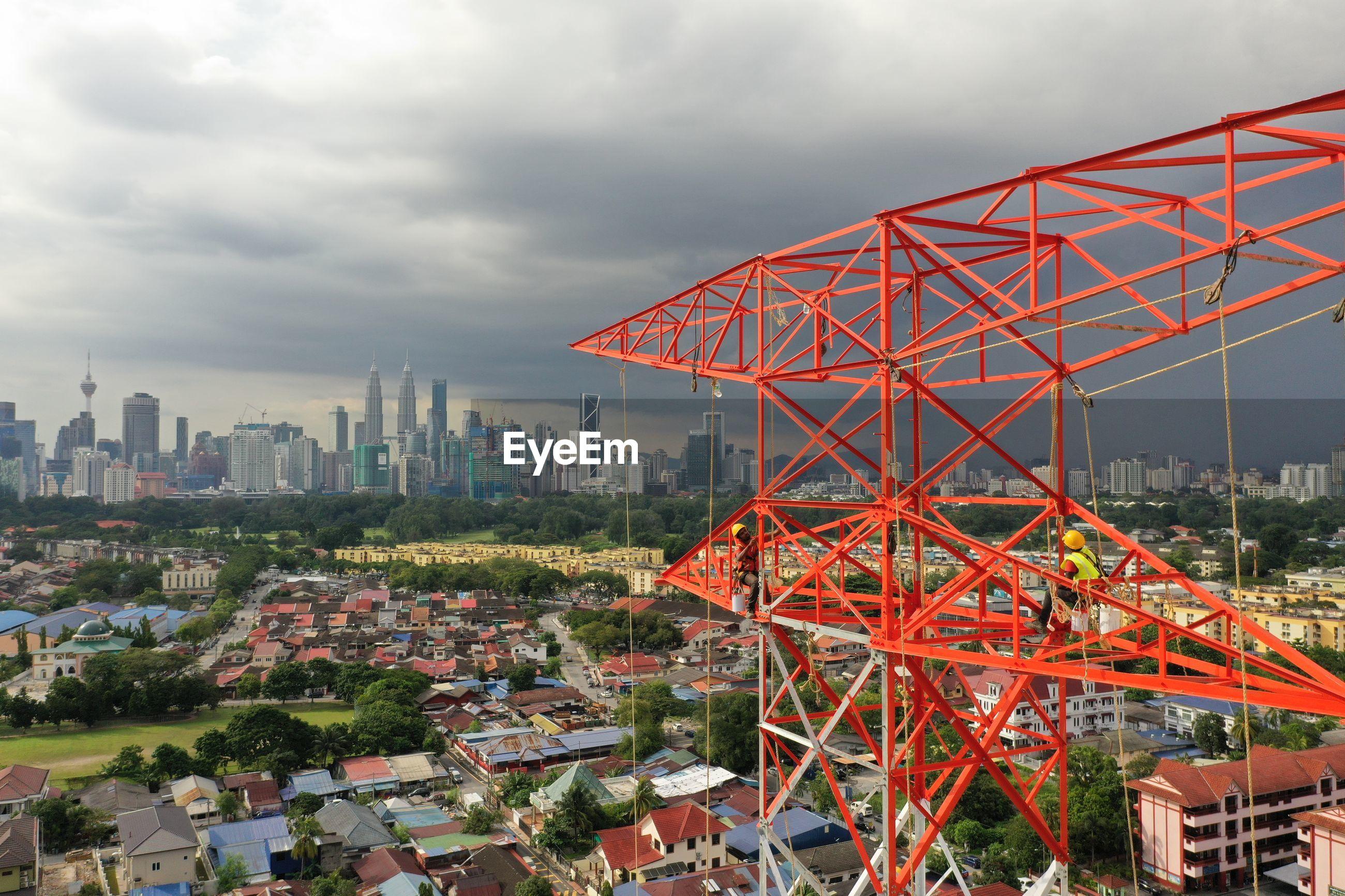 Ferris wheel by buildings against sky in city