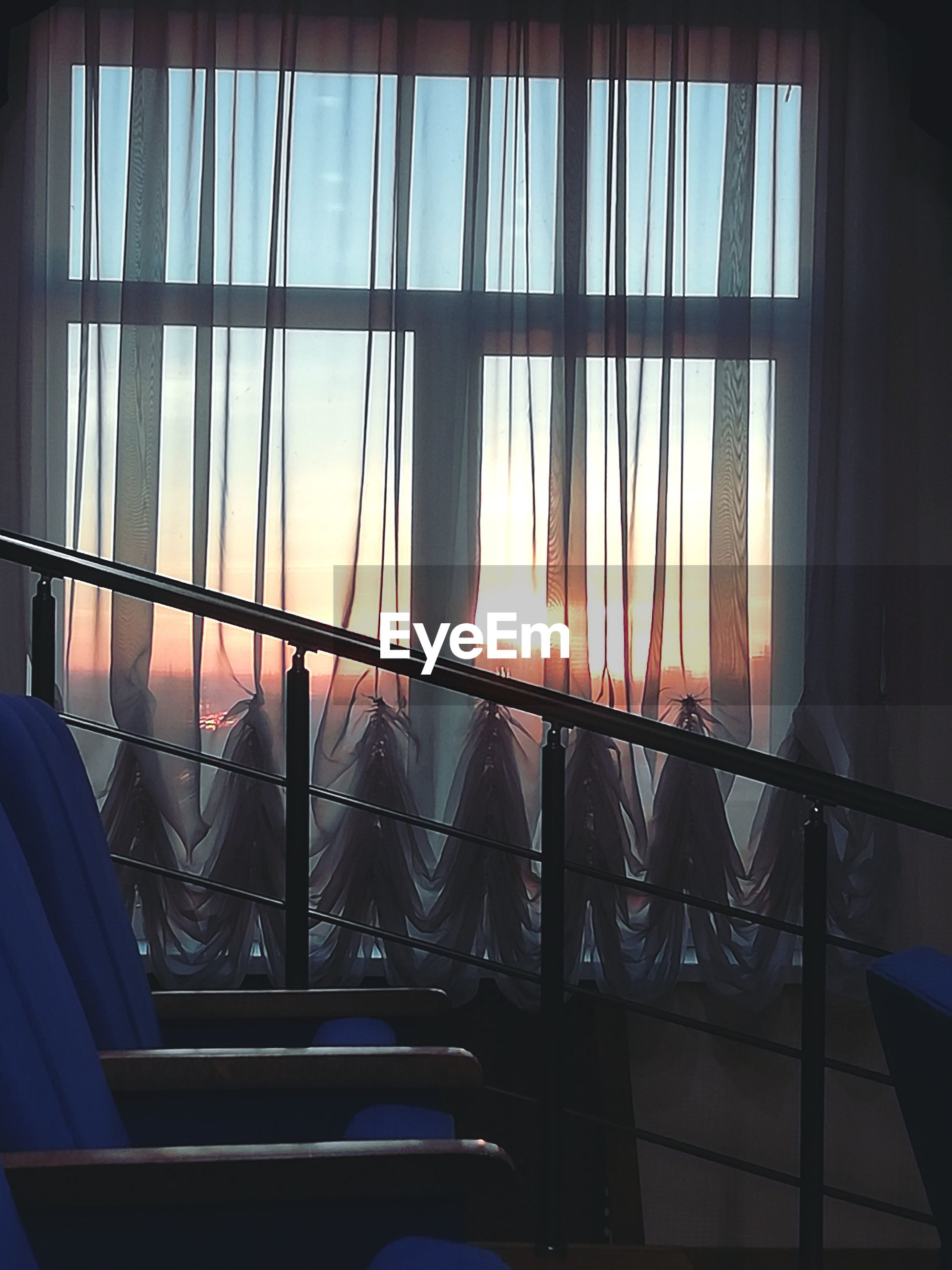 window, indoors, glass - material, transparent, curtain, no people, architecture, day, sky, nature, sunlight, built structure, seat, sunset, railing, chair, absence, low angle view