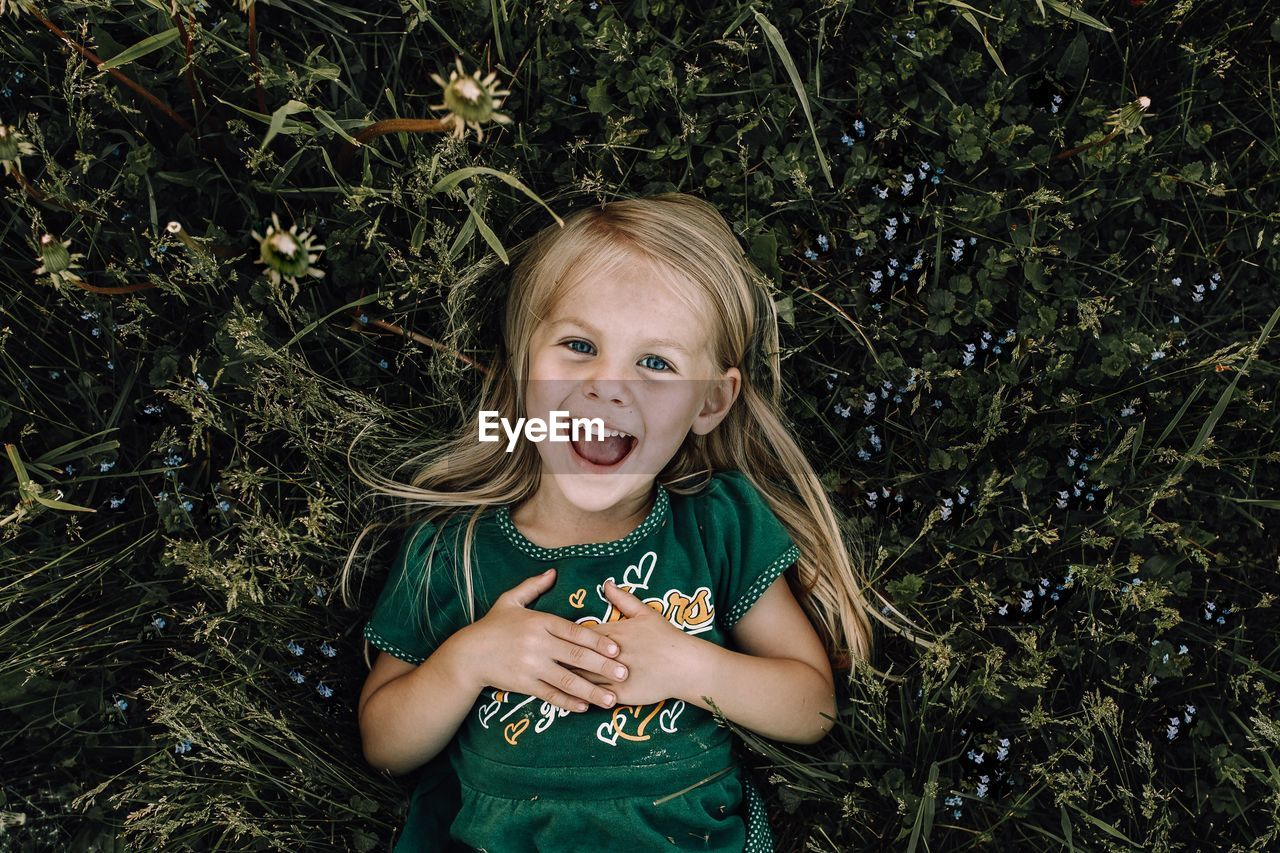 High angle portrait of smiling girl lying on plants