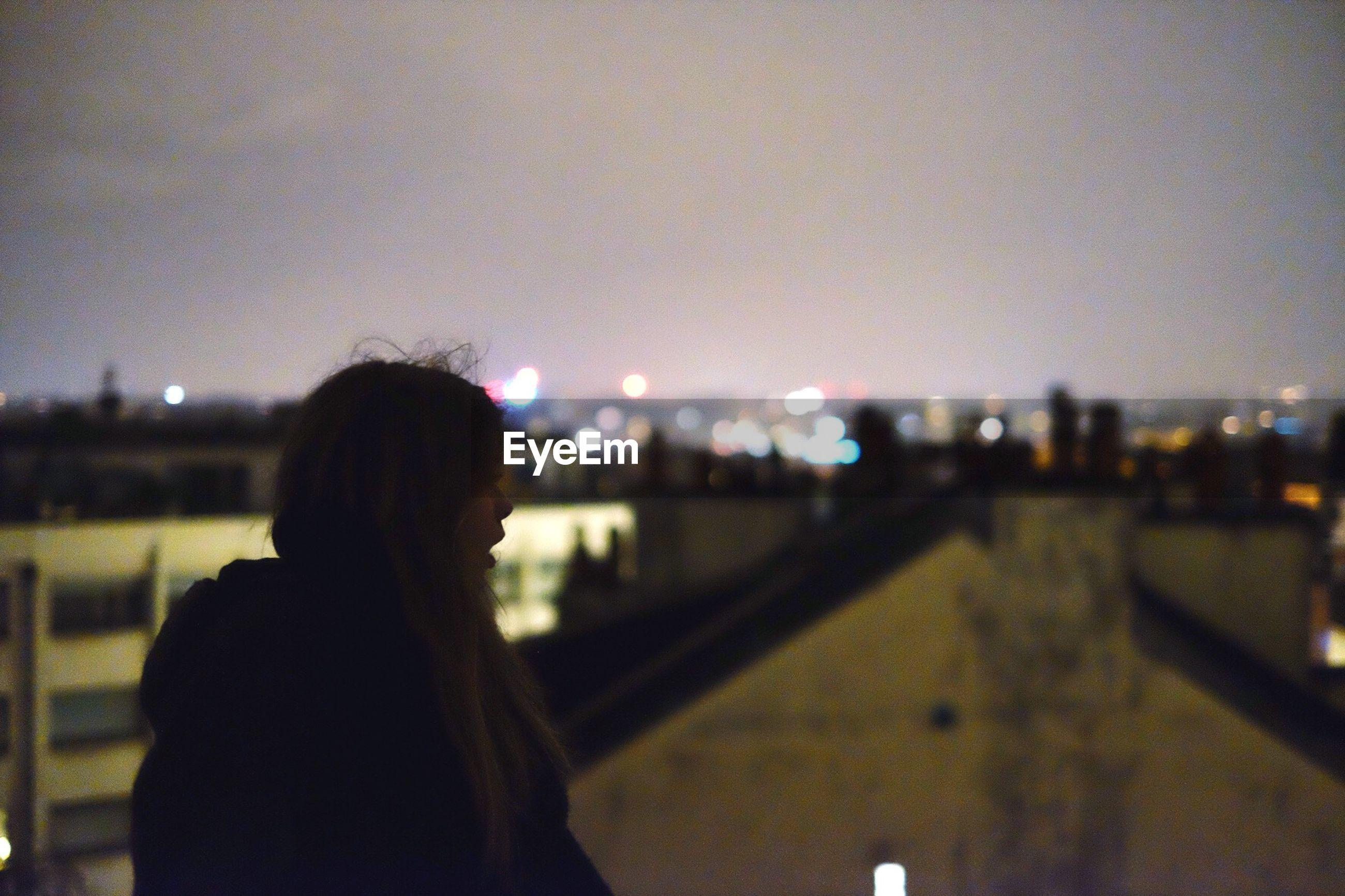 Girl standing on rooftop overlooking city