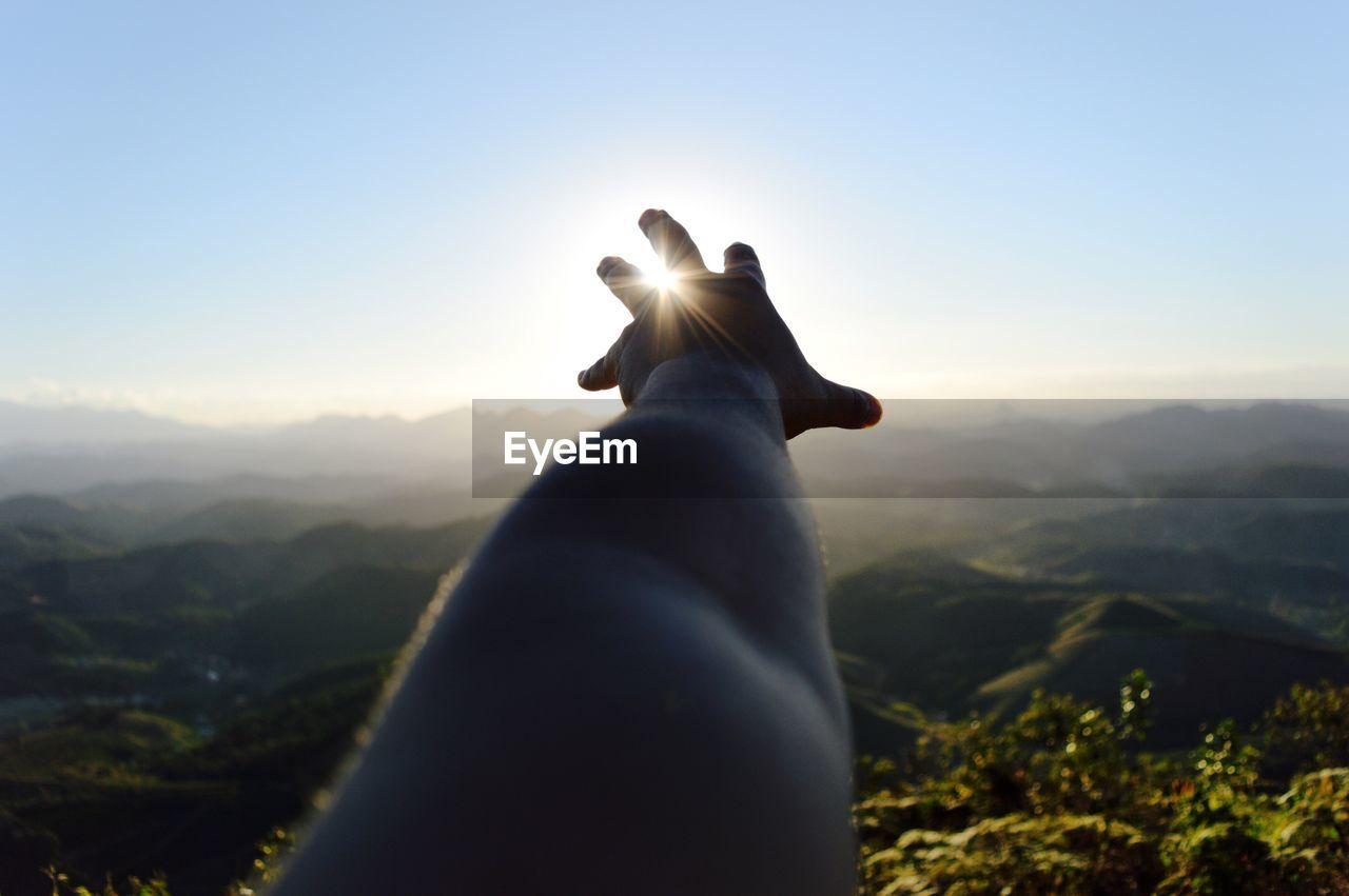 Cropped Image Of Person Hand Reaching Towards Sun