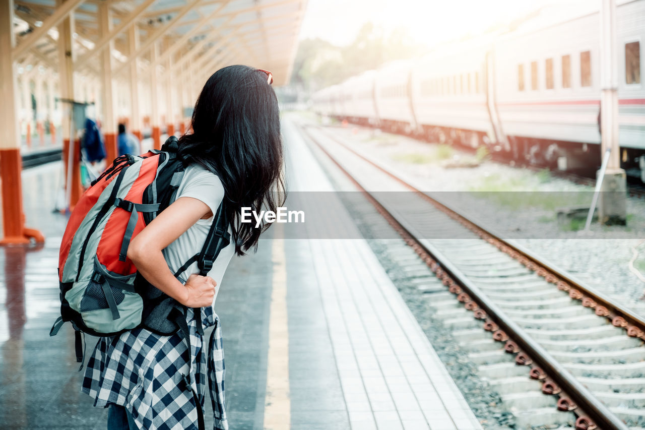 rail transportation, transportation, real people, railroad track, mode of transportation, track, travel, railroad station platform, women, one person, public transportation, lifestyles, focus on foreground, casual clothing, adult, railroad station, standing, backpack, three quarter length, hairstyle, waiting, teenager