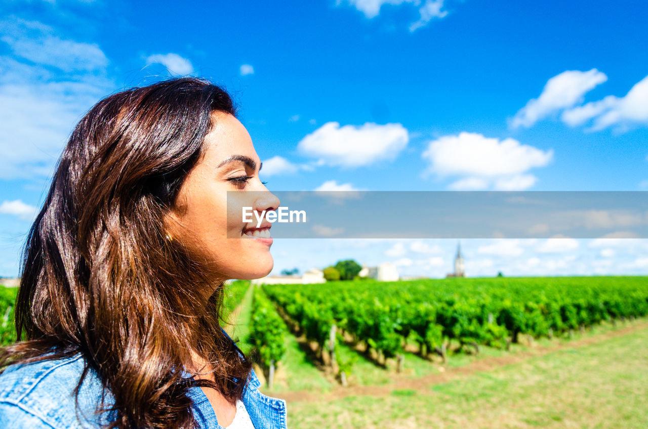 one person, field, land, real people, headshot, sky, nature, cloud - sky, lifestyles, smiling, young adult, adult, young women, environment, day, portrait, landscape, leisure activity, plant, women, hair, hairstyle, outdoors