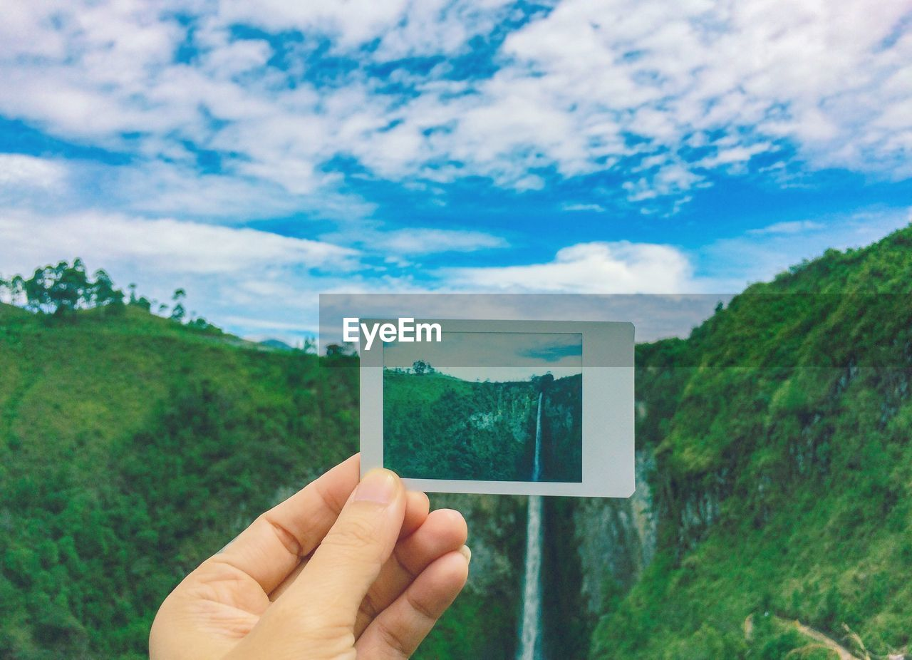 Cropped Hand Of Person Holding Instant Print Transfer Against Waterfall And Mountain