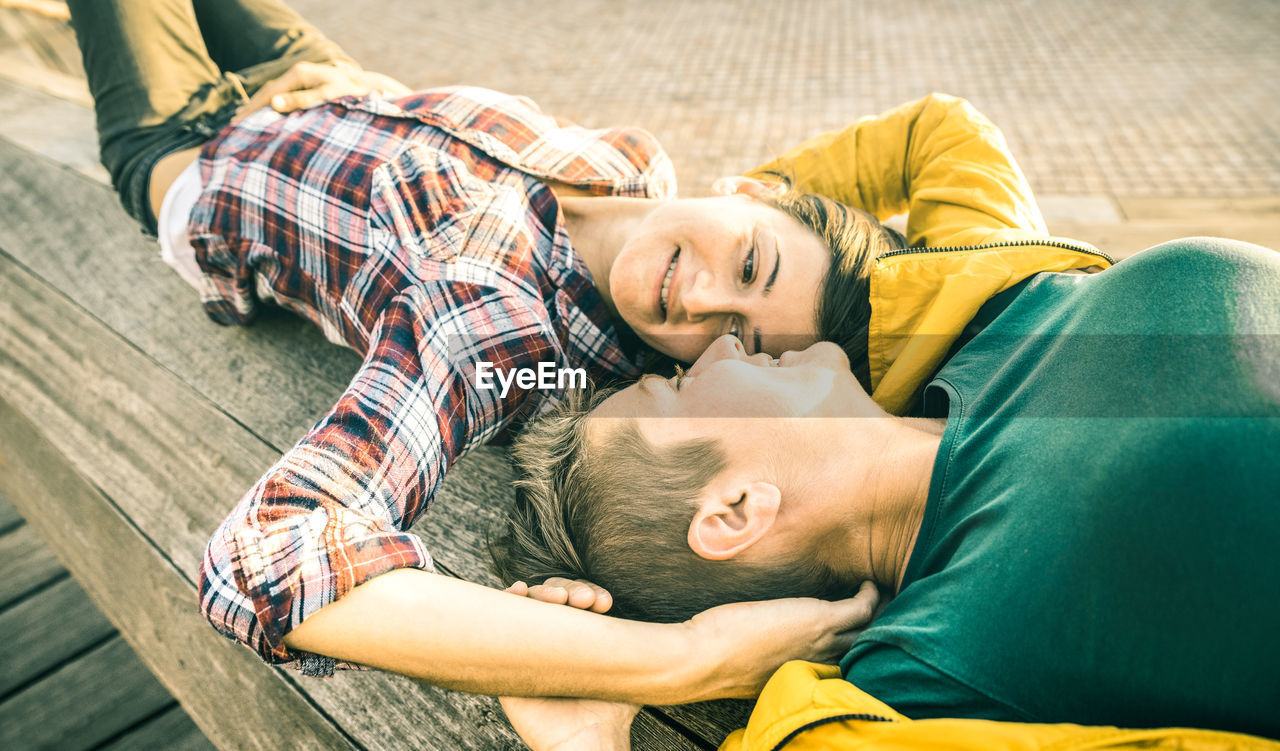 Lesbian couple lying on bench at park