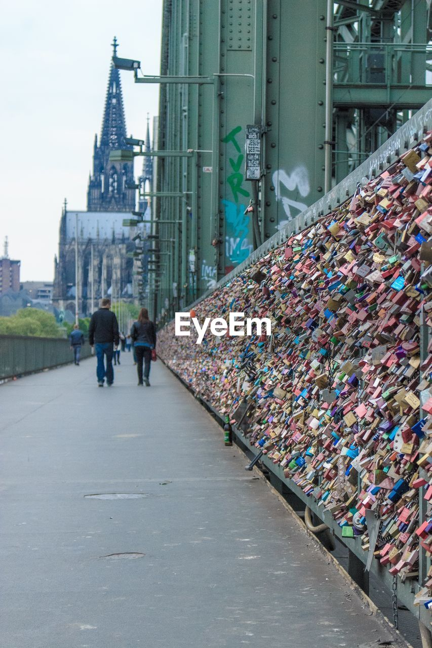 architecture, love lock, padlock, built structure, love, bridge - man made structure, outdoors, day, men, real people, building exterior, city, people