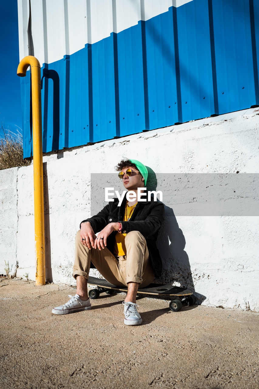 Young man wearing sunglasses sitting on skateboard against wall