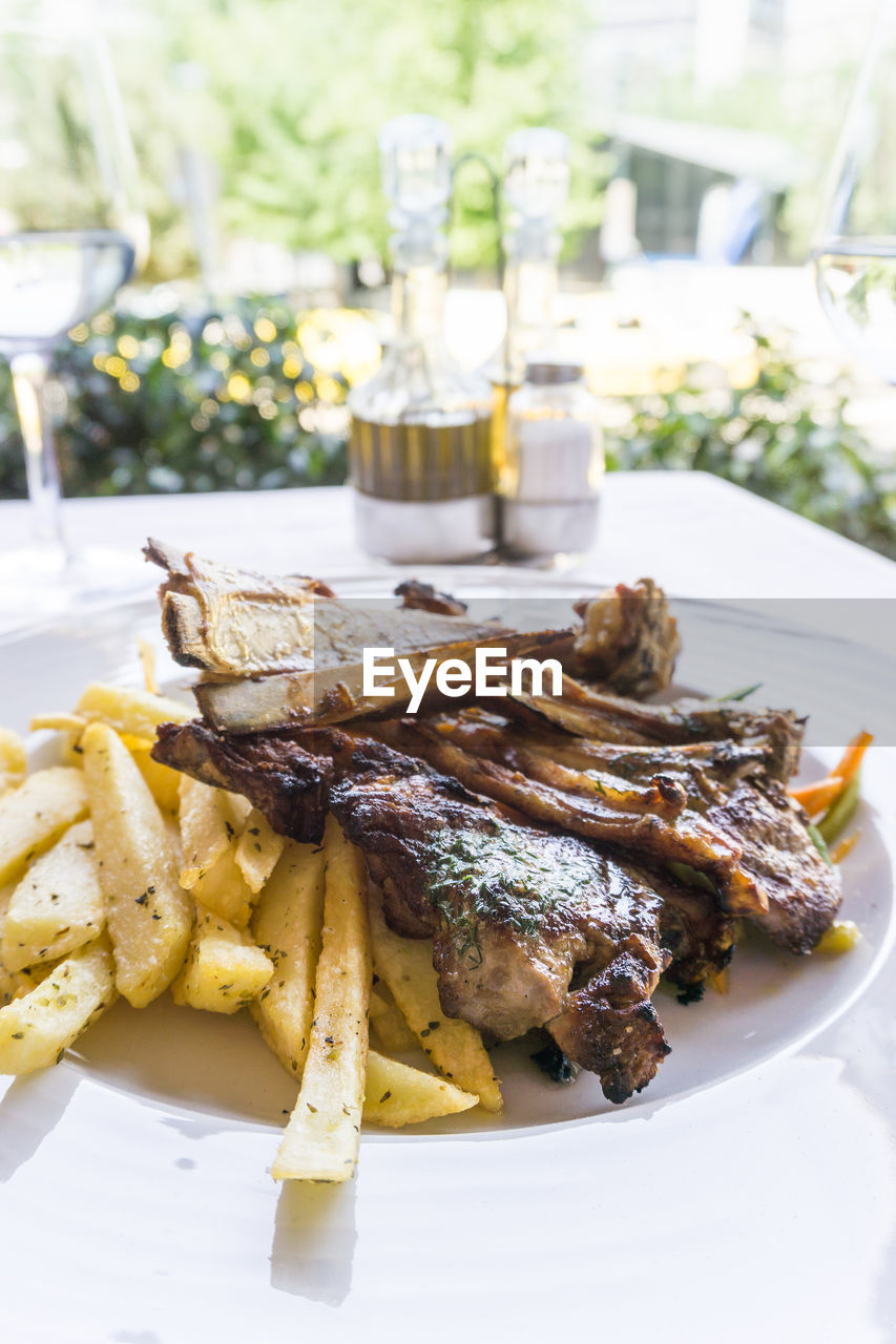 Close-up of lamb chops with french fries served in plate on table