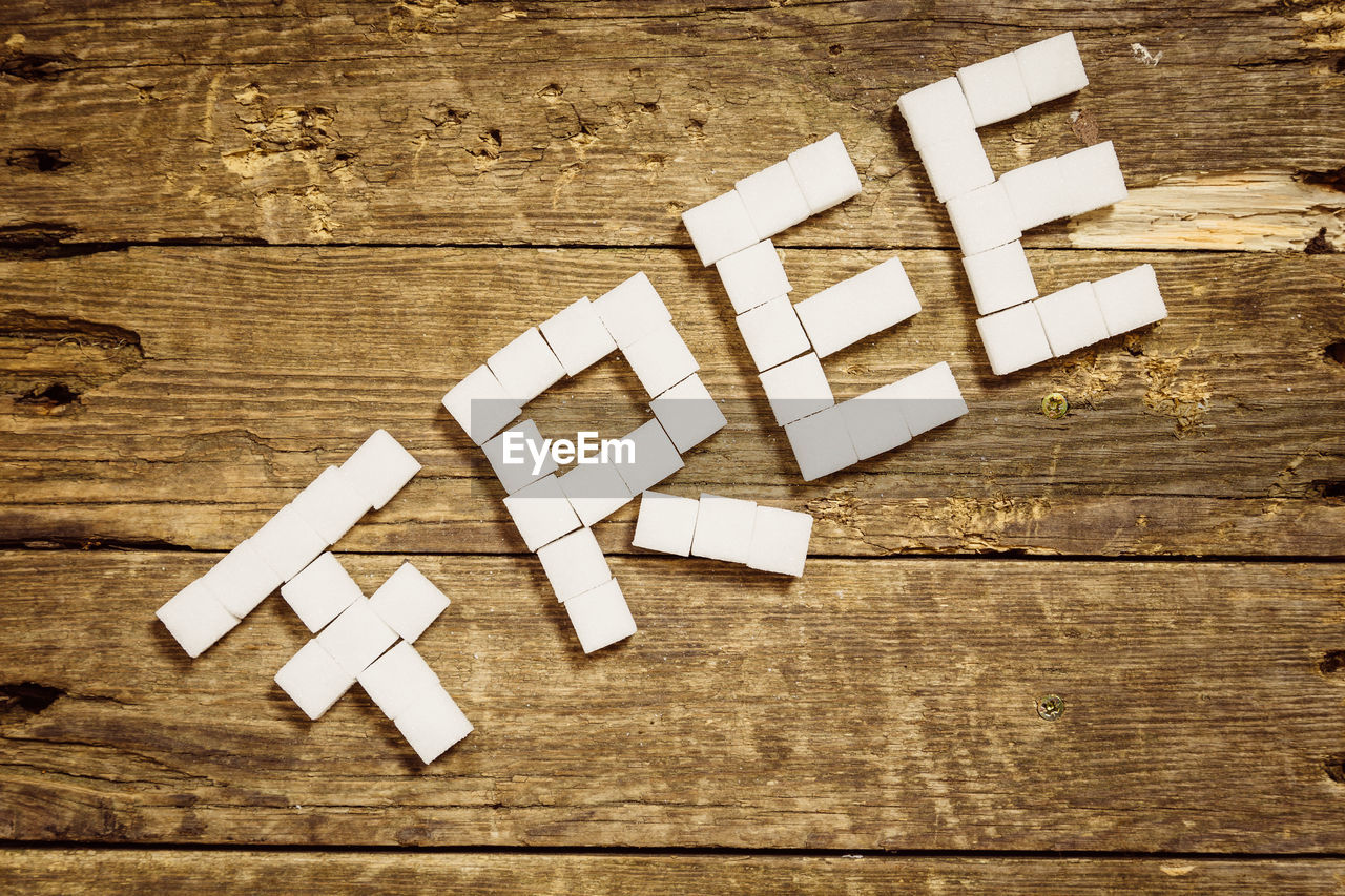 wood - material, indoors, table, still life, no people, text, white color, directly above, high angle view, wood, western script, capital letter, communication, large group of objects, creativity, toy block, paper, arrangement, close-up, wood grain, blank