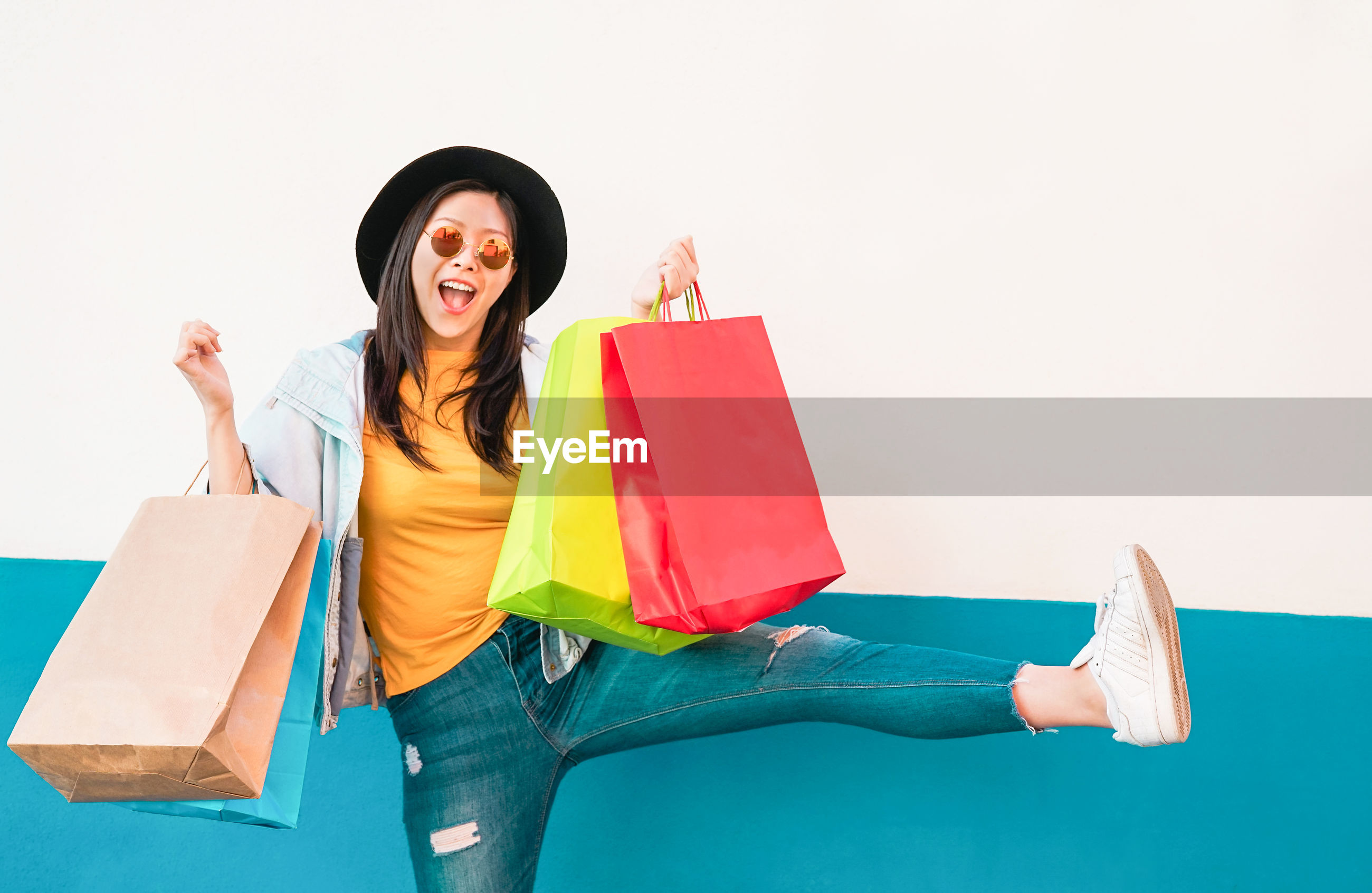 Young woman wearing sunglasses while holding shopping bags against wall