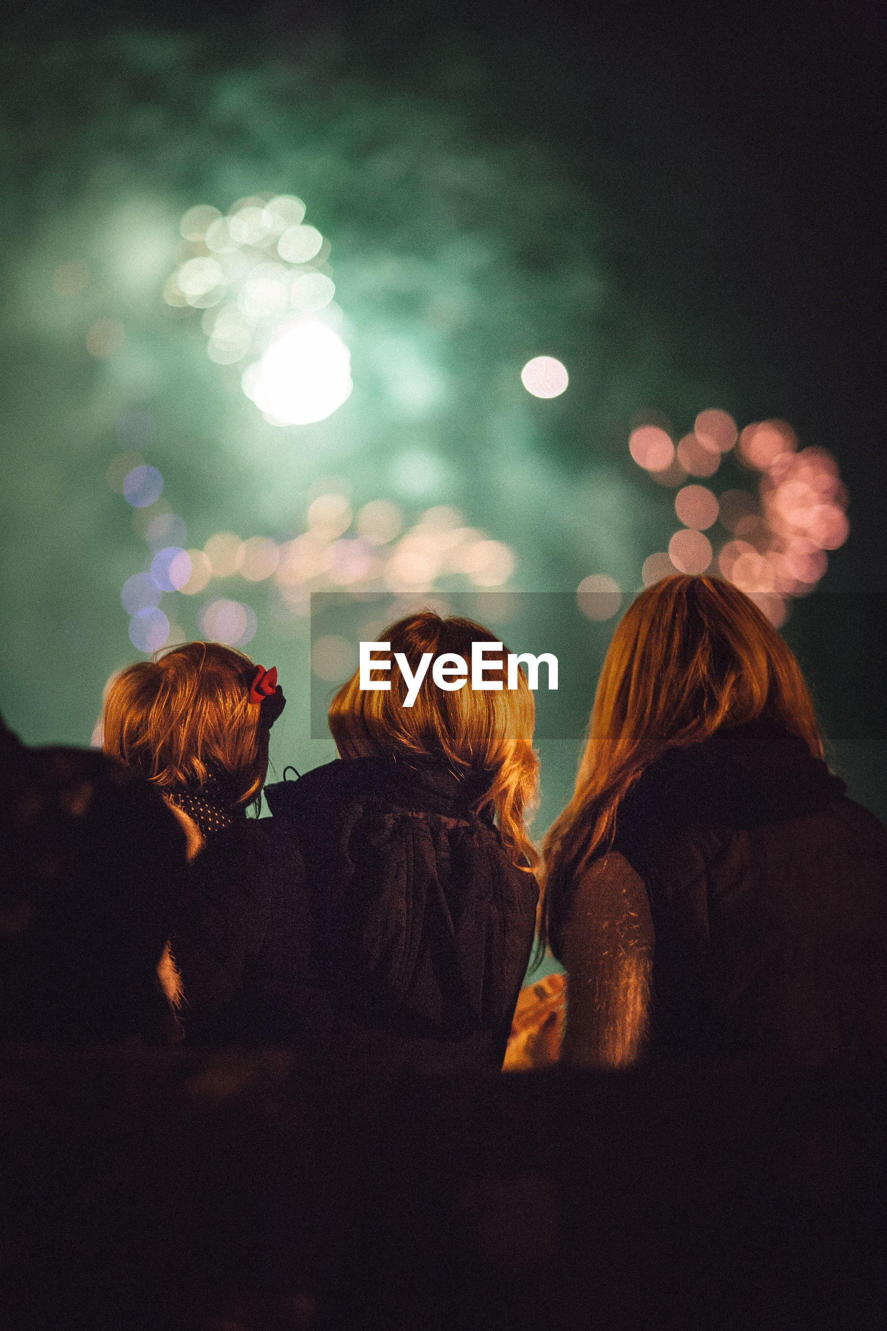 Low angle view of family against illuminated fireworks at night