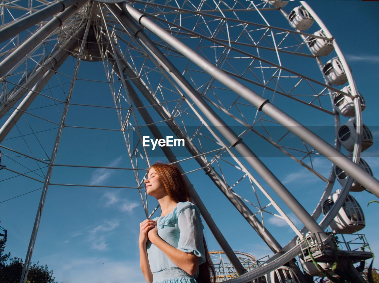 amusement park ride, leisure activity, amusement park, low angle view, ferris wheel, real people, sky, lifestyles, one person, day, nature, casual clothing, young adult, arts culture and entertainment, young women, enjoyment, child, looking, outdoors, hairstyle