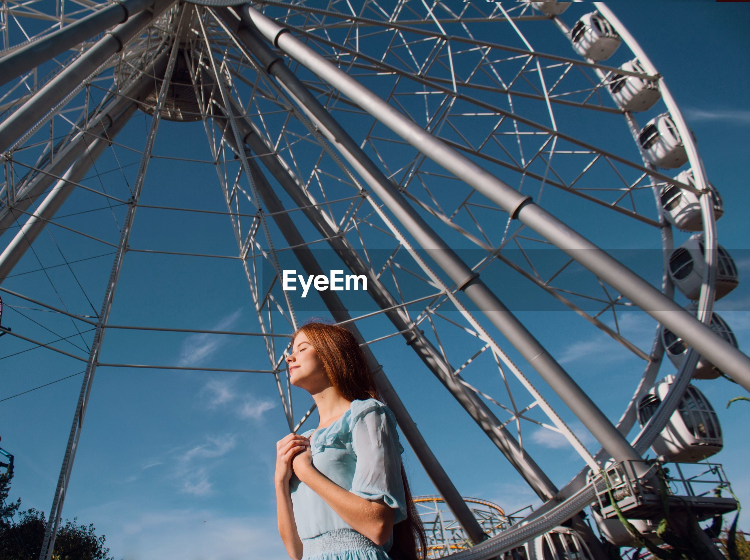 LOW ANGLE VIEW OF YOUNG WOMAN LOOKING AT AMUSEMENT PARK