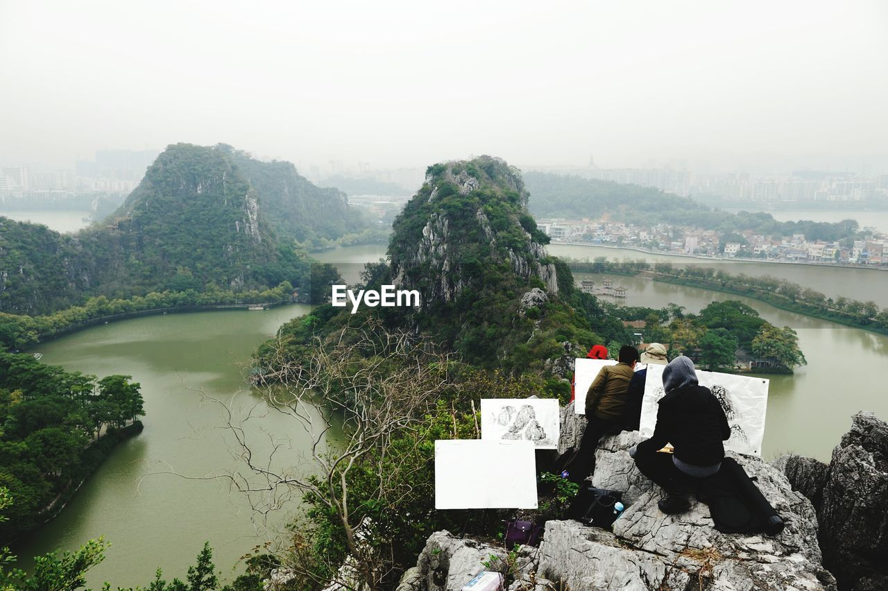 Rear View Of People Painting On Canvas Against River And Mountains During Foggy Weather