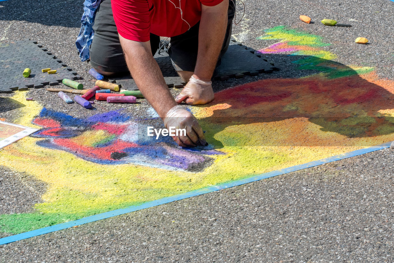multi colored, creativity, art and craft, real people, one person, street, men, day, low section, paint, chalk drawing, high angle view, chalk - art equipment, drawing - art product, city, leisure activity, road, lifestyles, craft, messy