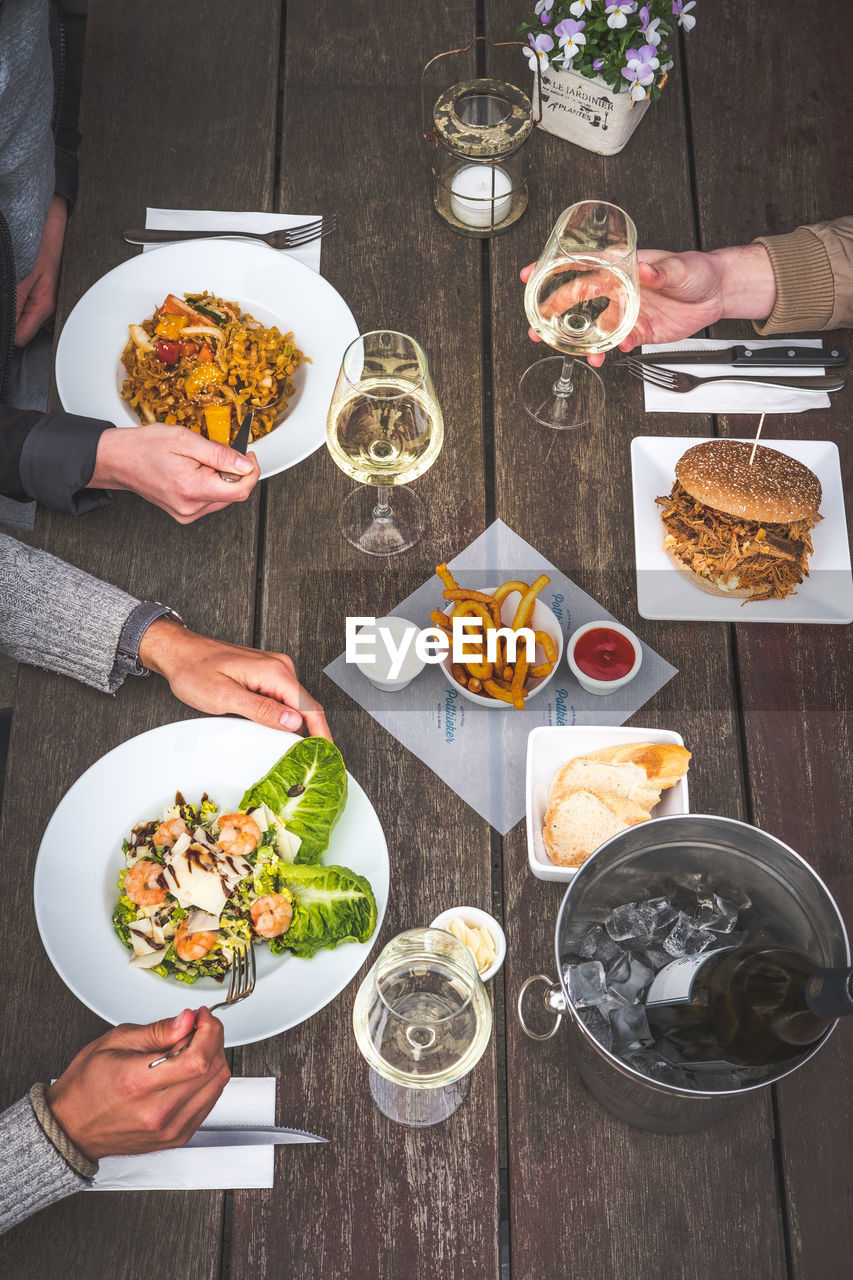 food and drink, table, food, human hand, plate, hand, freshness, human body part, drink, glass, real people, group of people, men, ready-to-eat, holding, high angle view, togetherness, people, refreshment, lifestyles, meal