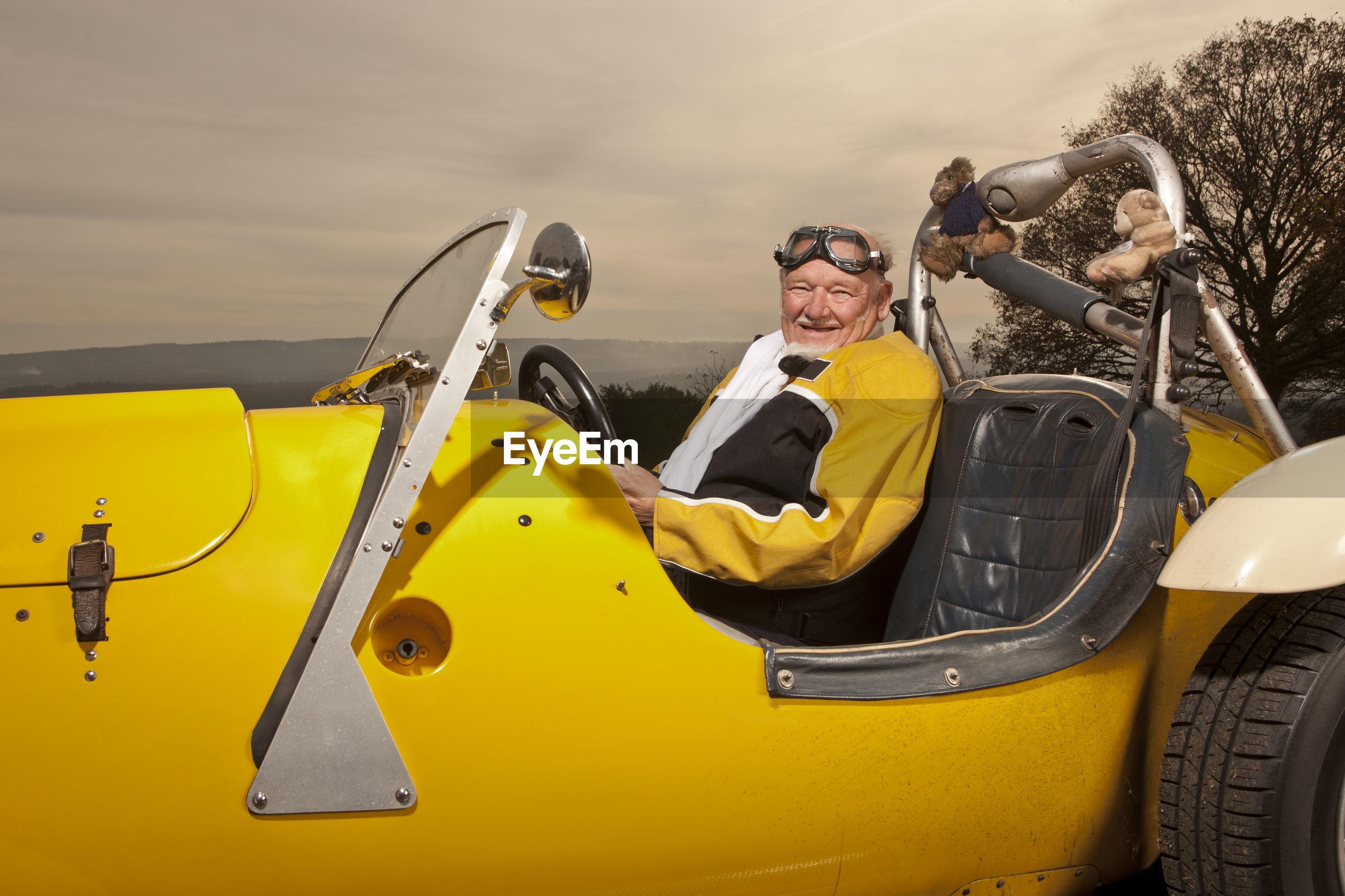 PORTRAIT OF HAPPY MAN SITTING ON YELLOW CART
