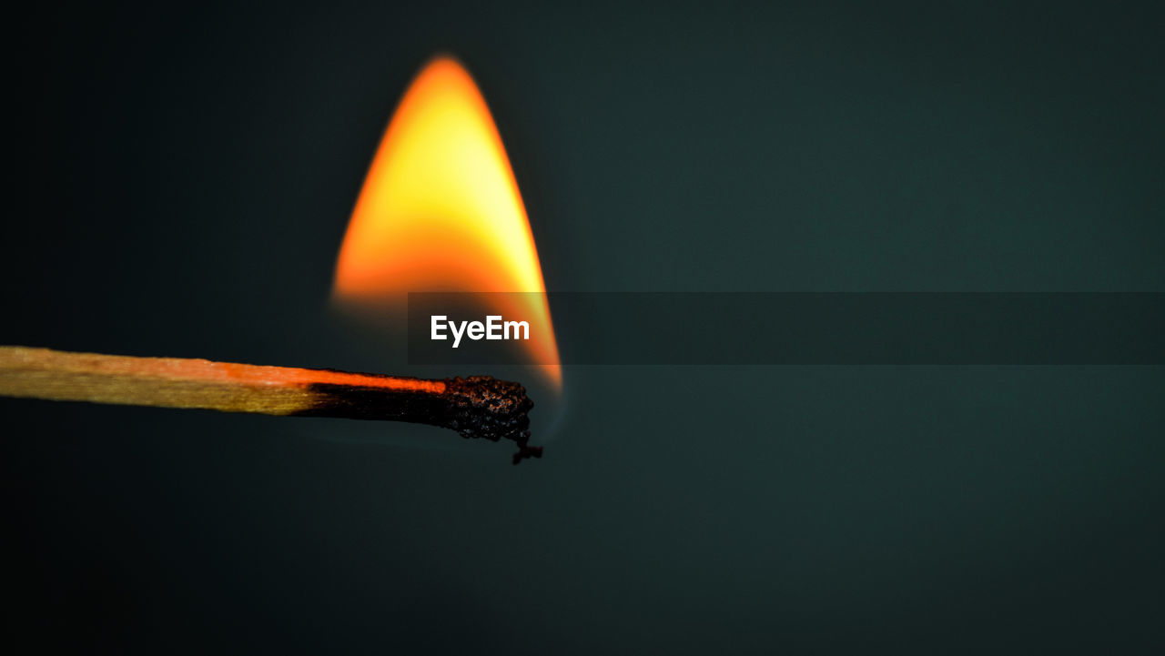 Close-up of burning matchstick over gray background