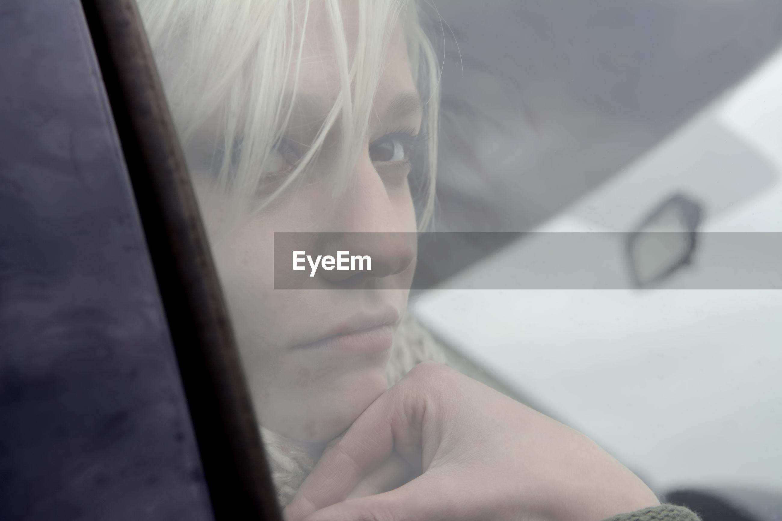 Close-up of woman seen through car glass window