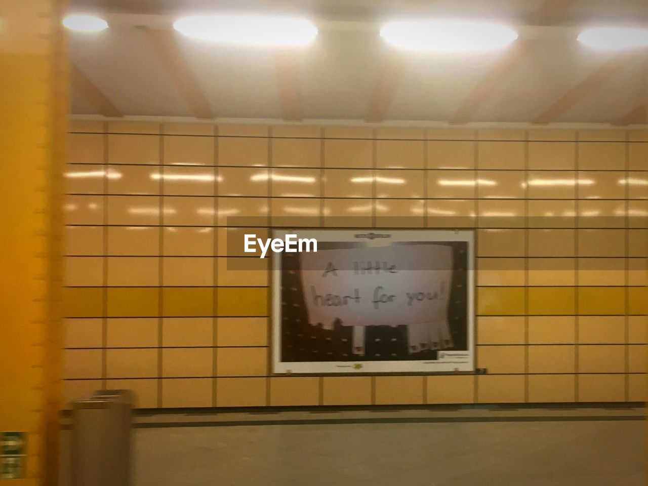 illuminated, indoors, lighting equipment, no people, wall - building feature, text, tile, flooring, communication, light, ceiling, subway station, western script, architecture, public restroom, domestic room, electric light, wall, sign, public building